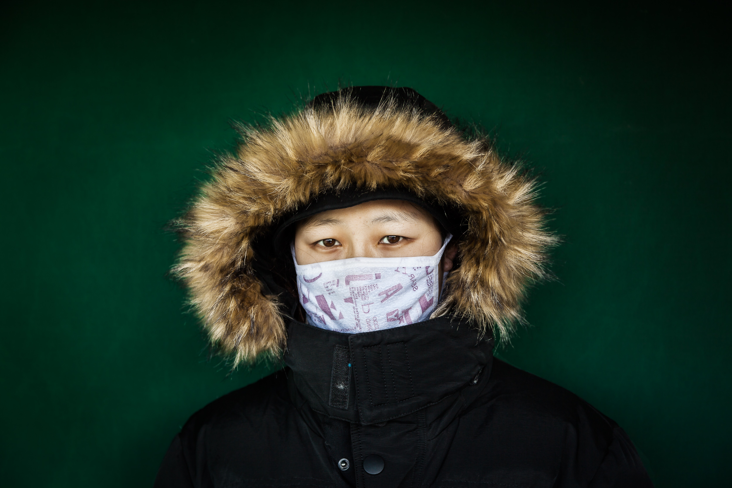A young woman , wrapped in a hooded jacket , makes for a colorful composition placed against a deep green colored wall in Beijing, China