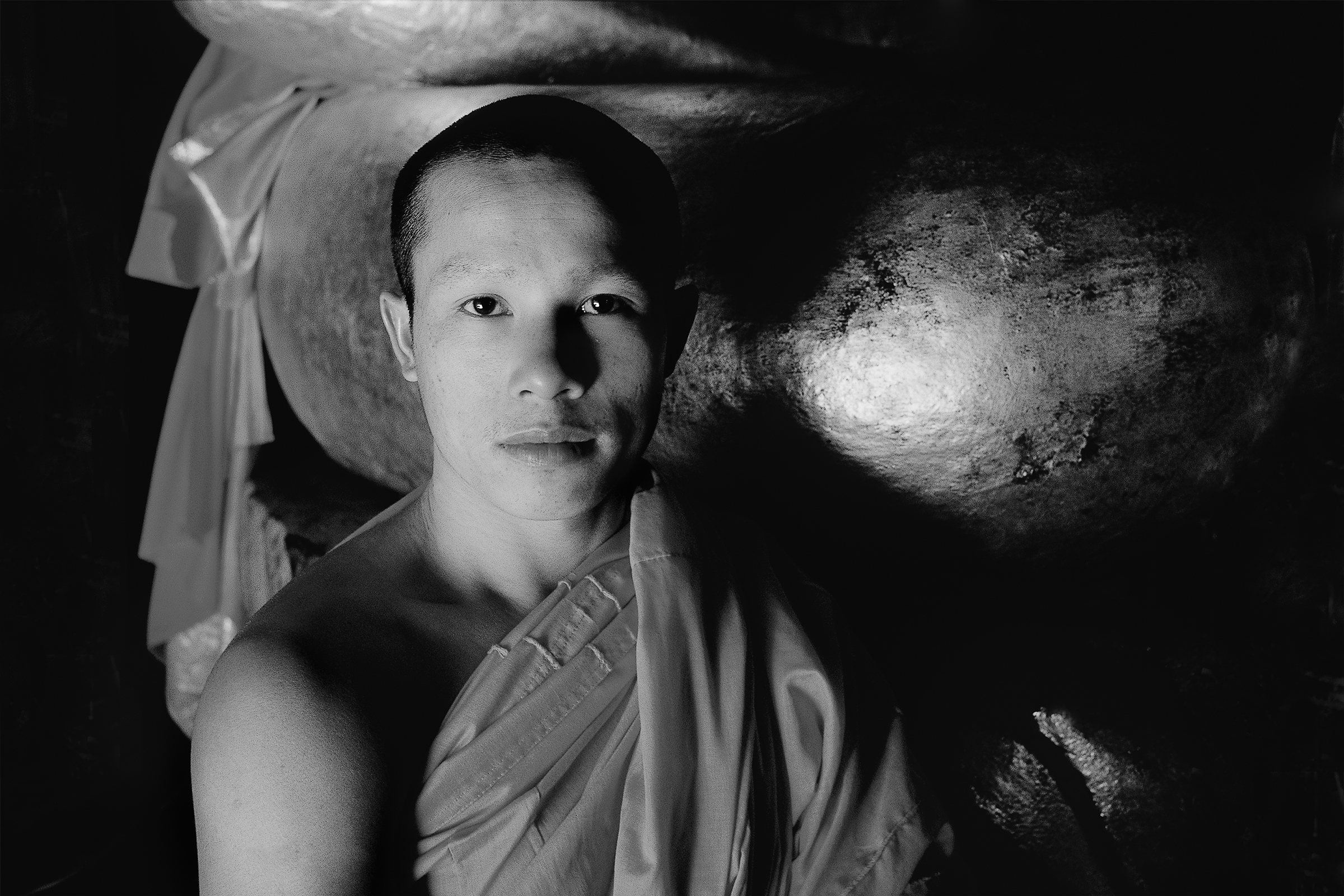A formal portrait of a    Buddhist monk   , bathed in window light, in    Luang Prabang, Laos   .