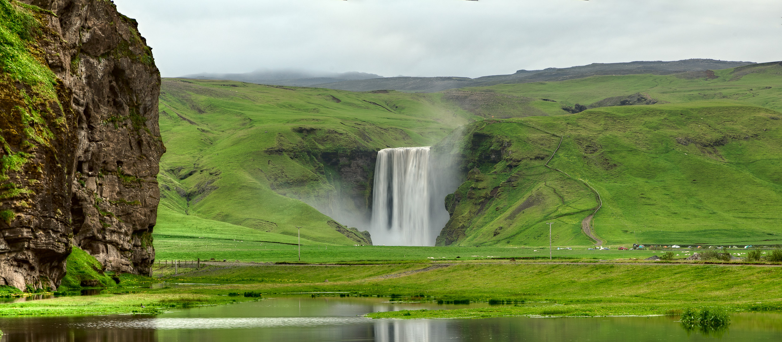 The powerful  Skógafoss Waterfall  depicted within the larger lush green landscape of  southern Iceland .