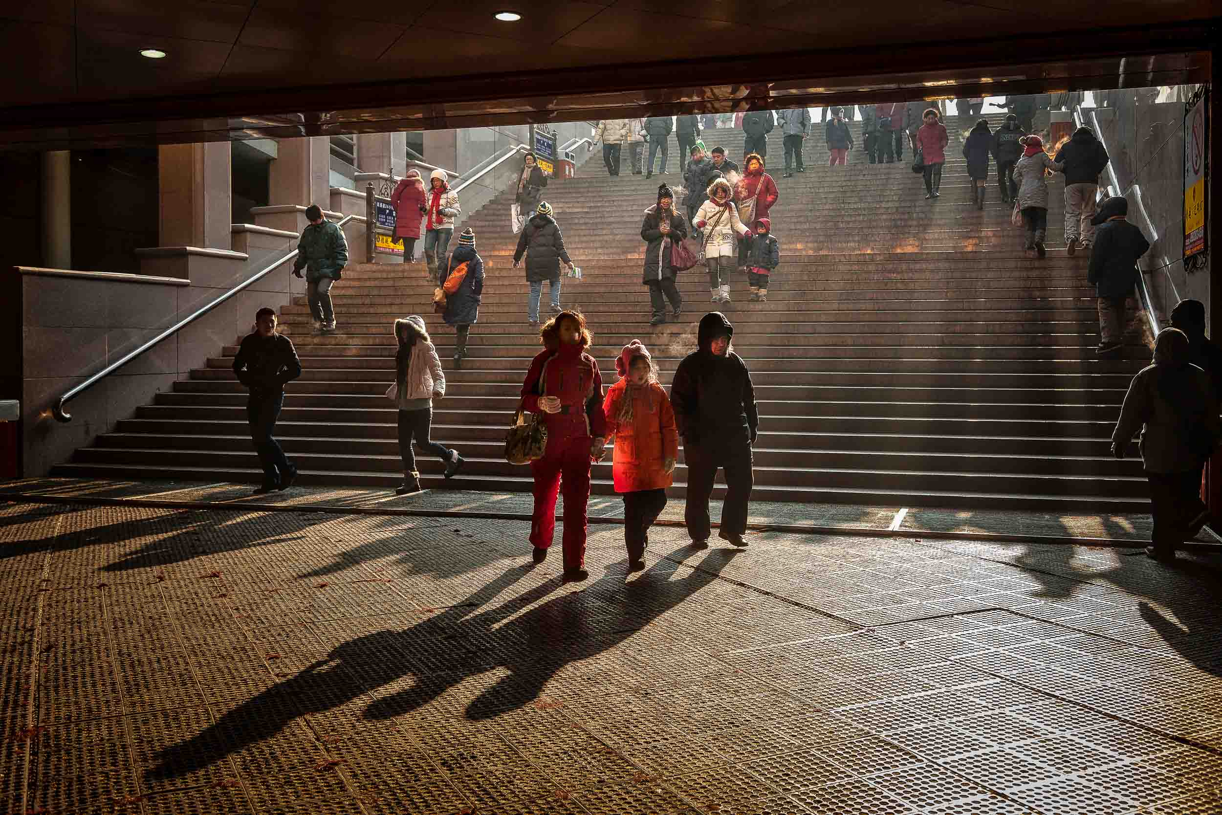 A family make their way into a subway on a    cold winter's day    in    Harbin, China   . China holidays provide so many glimpses into the Human Condition.
