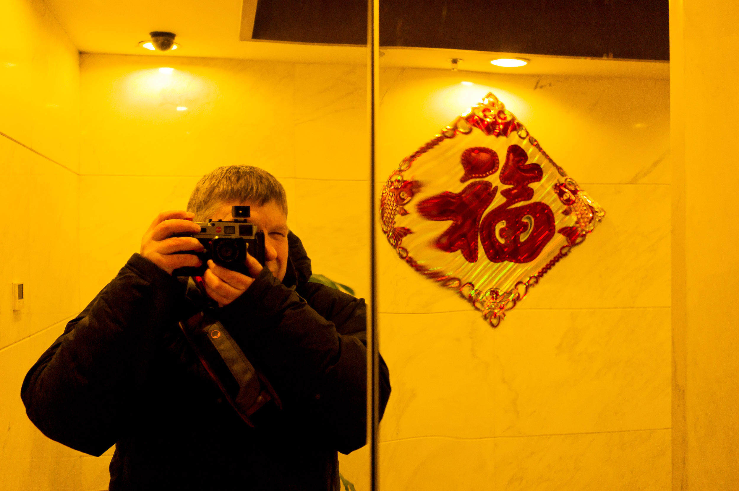 A self portrait of    Glenn Guy, the Travel Photography Guru   , formed on a shinny set of lift doors in a hotel in Beijing, China. Not the most common China tourism experience, I grant you.