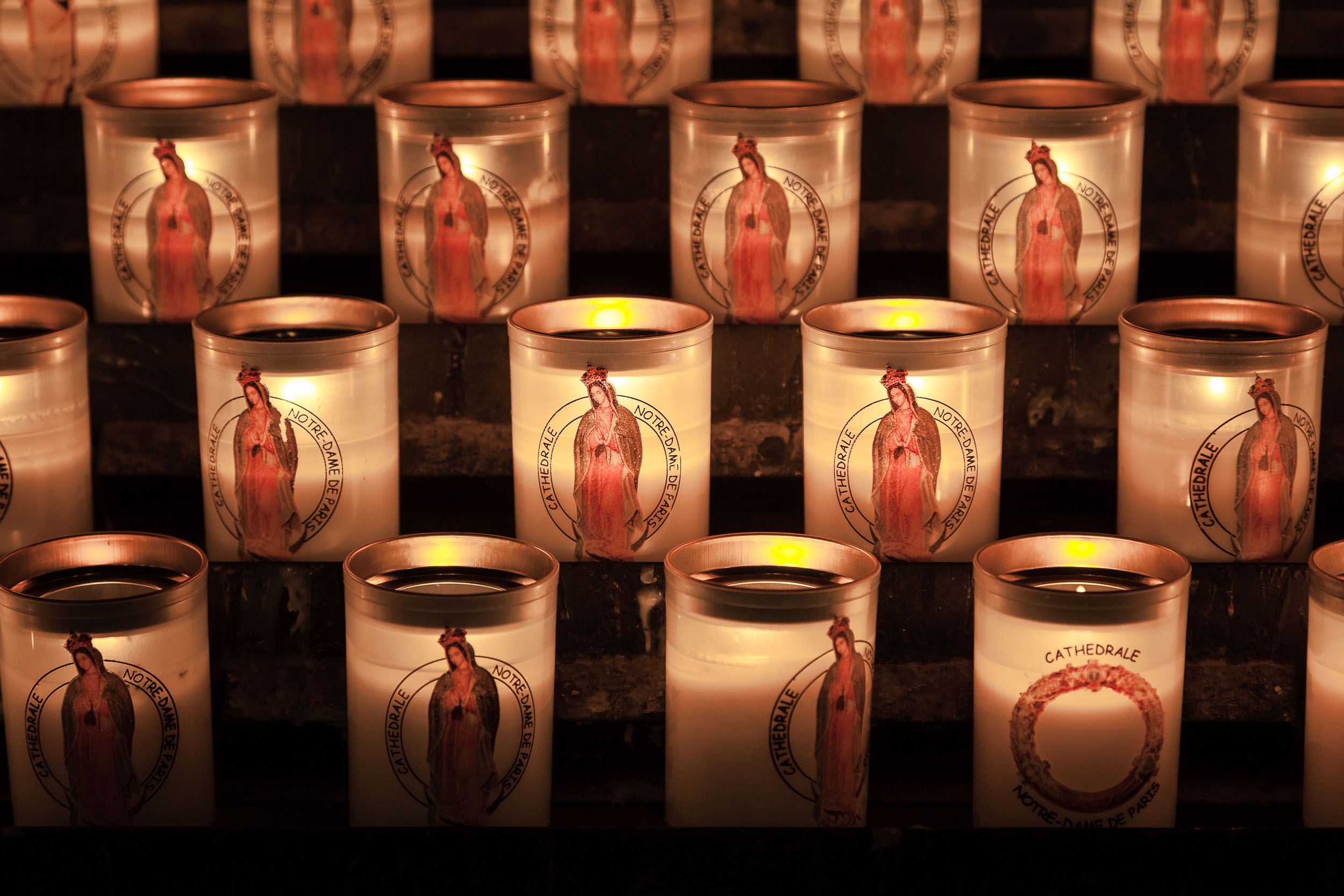 A close up view of  candles , featuring the  Virgin Mary , inside the  Notre Dame Cathedral  in Paris, France with a more  antique rendering of color .