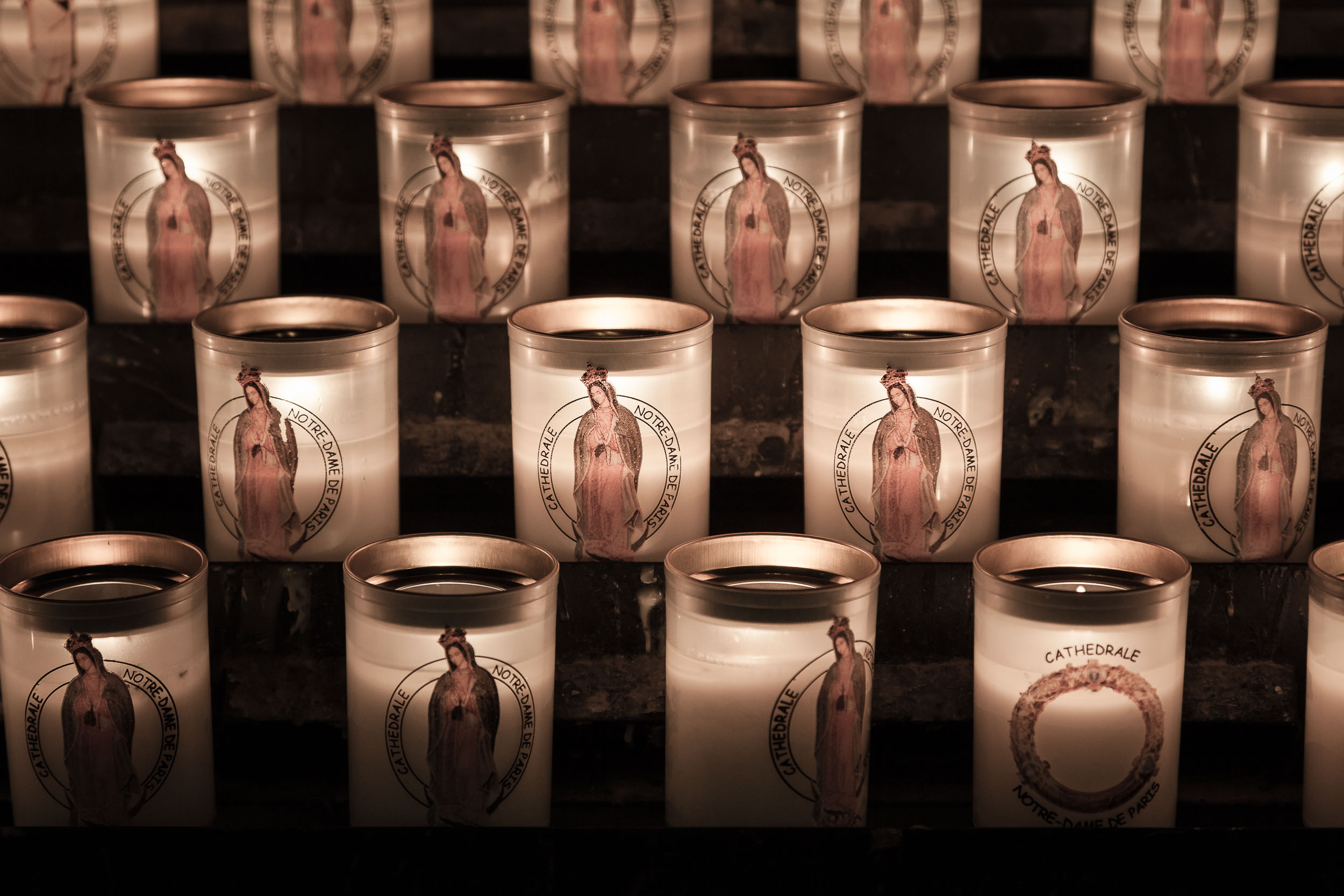 A close up view of  candles , featuring the  Virgin Mary , inside the  Notre Dame Cathedral  in Paris, France. This version shows a  subtle pink color rendering  in the candles.