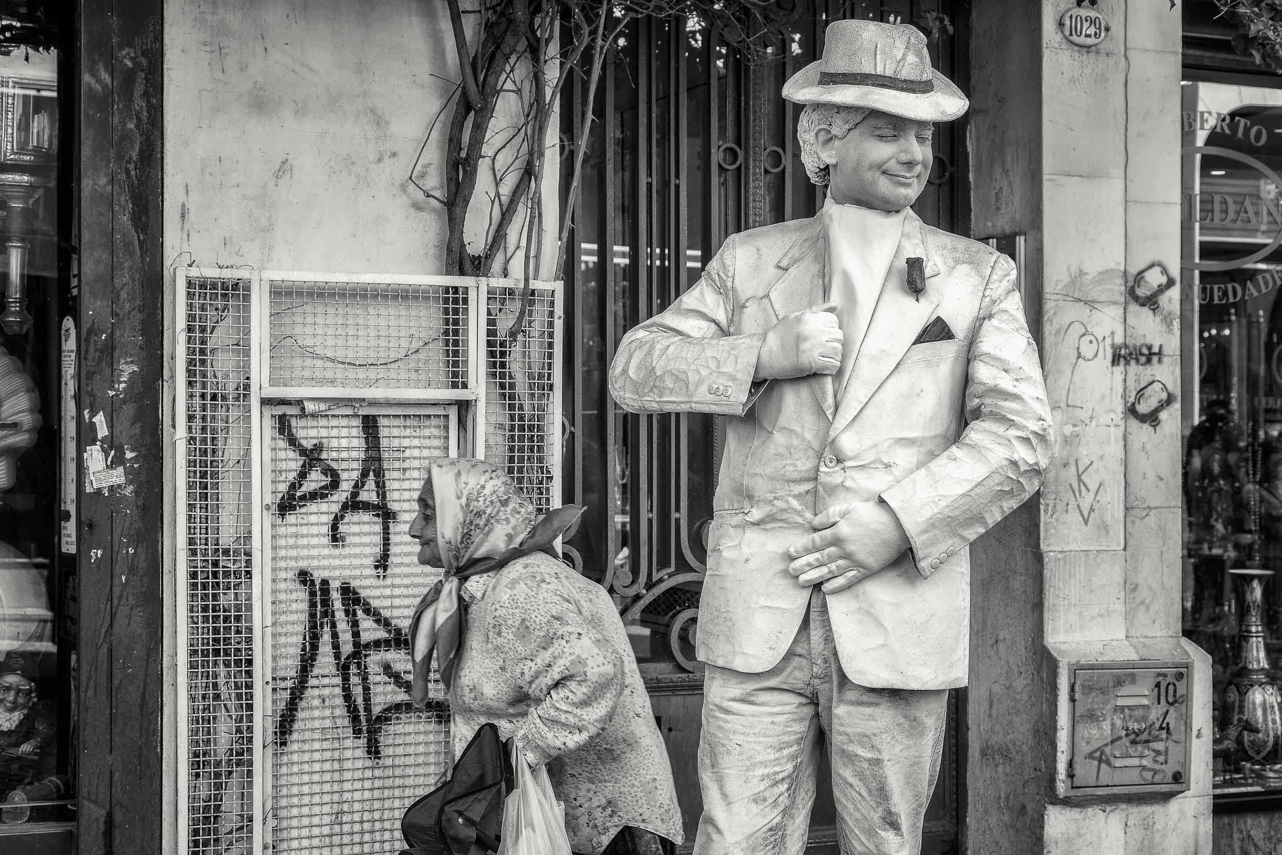 A classic street scene featuring a street performer and an elderly passerby in San Telmo, Buenos Aires, Argentina.