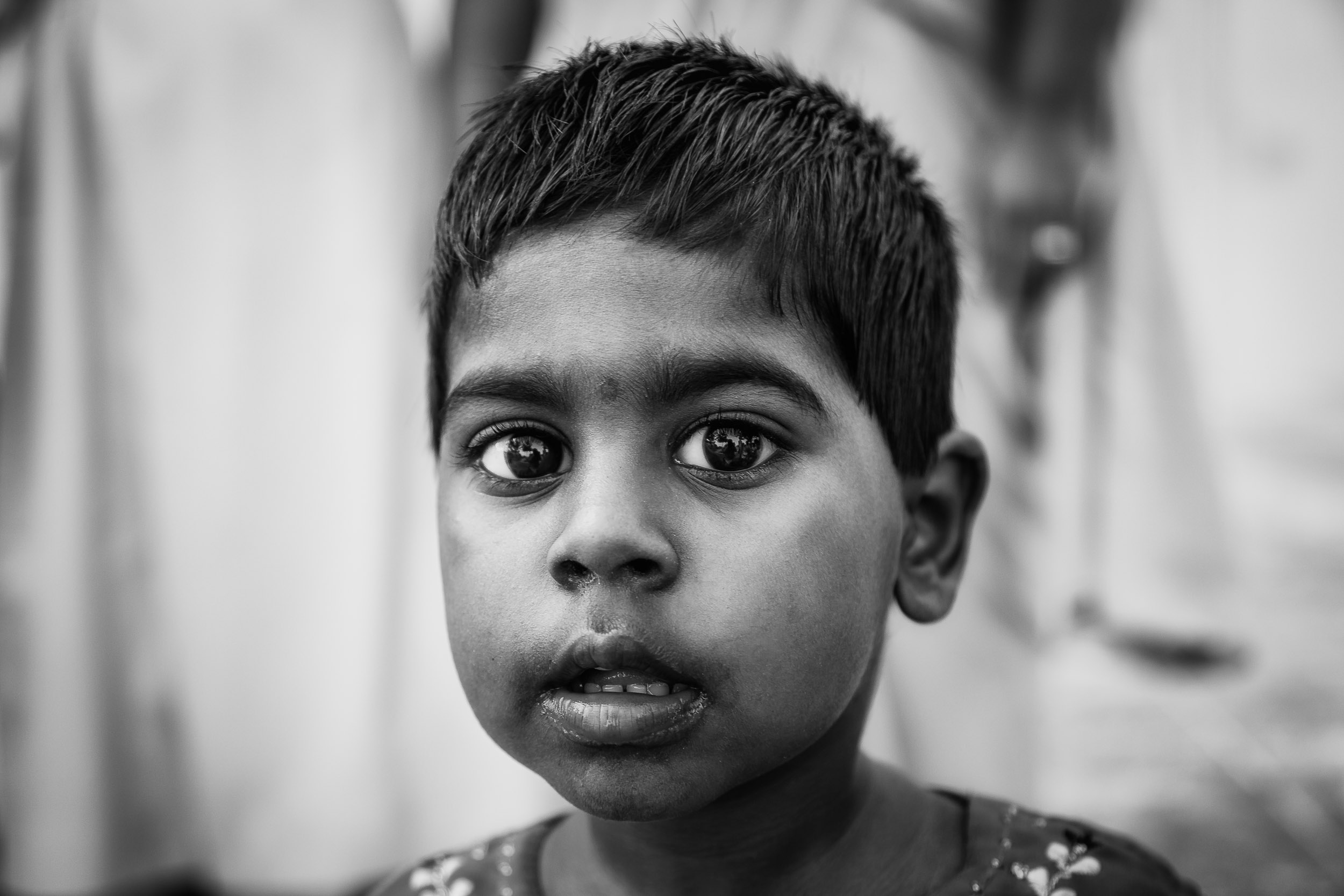 This girl is not a beggar.  She was well cared for at a  Catholic Orphanage  on the outskirts of  Chennai, India . The photographic event was supervised. You can see two nuns, whom I've put out of focus, standing directly behind the young girl.