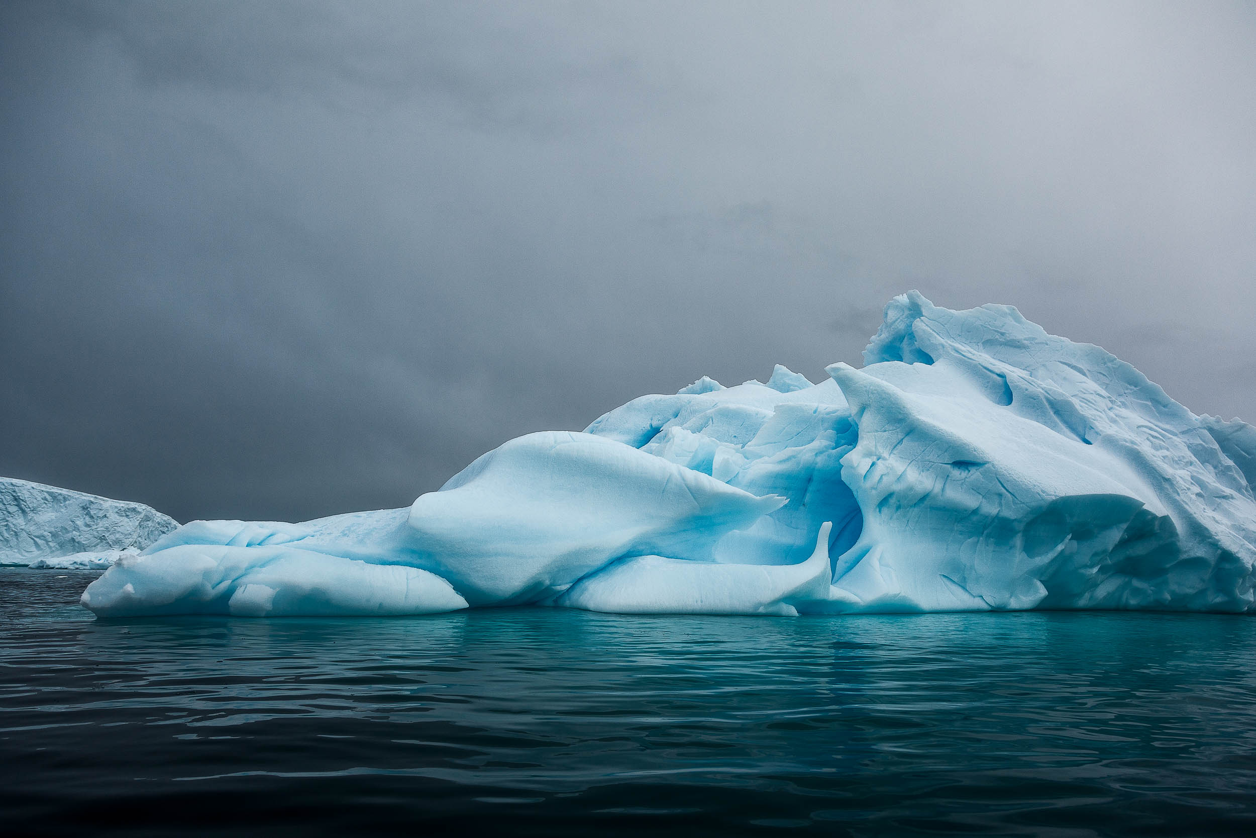 The top of an Iceberg on aqua waters under a mournful sky off Cuverville Island in Antarctica.