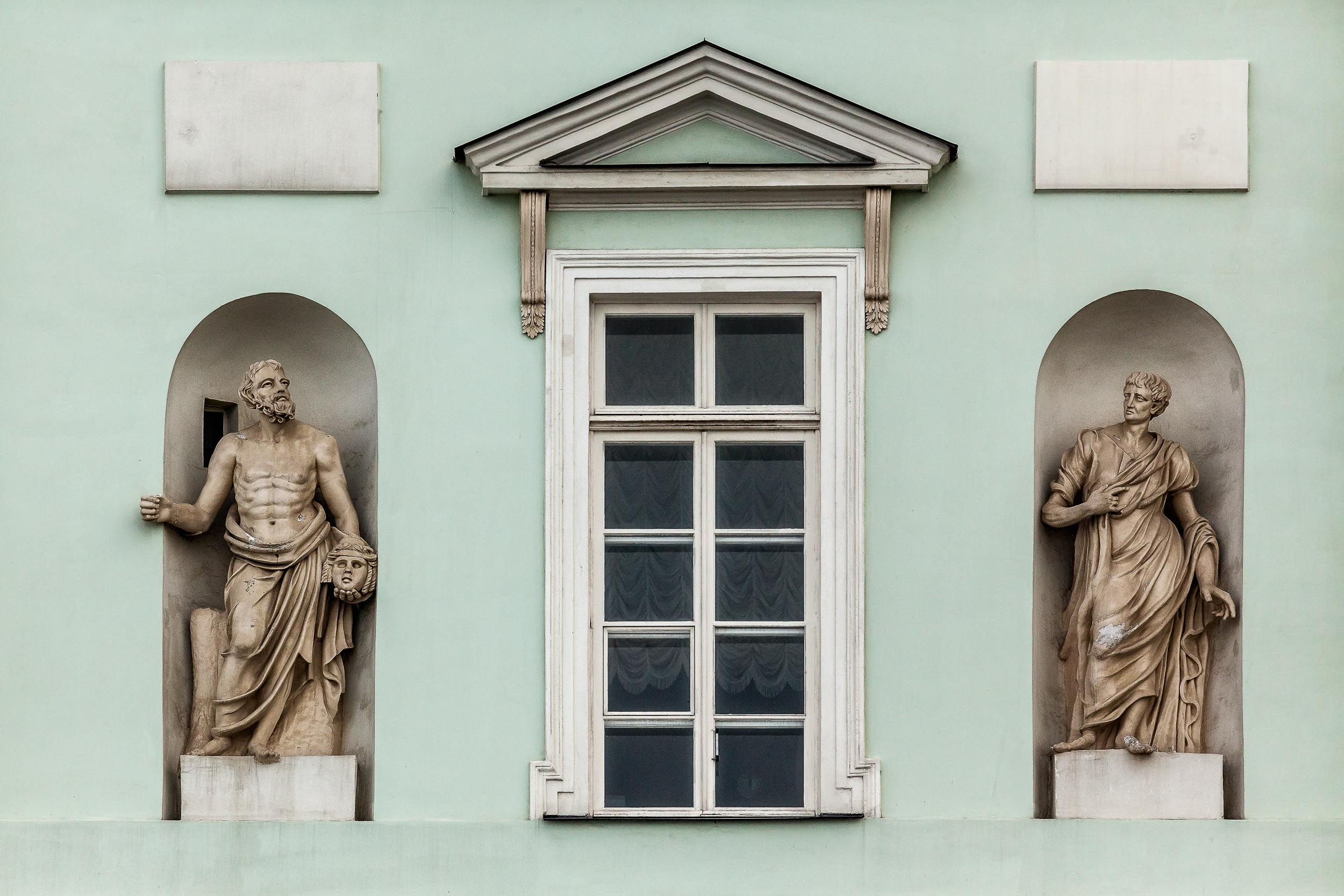 These  two statues , on either side of a window, is just one of hundreds of fascinating sites from a  canal cruise  in  St. Petersburg, Russia . This photo is composed very much around the notion of  symmetry .