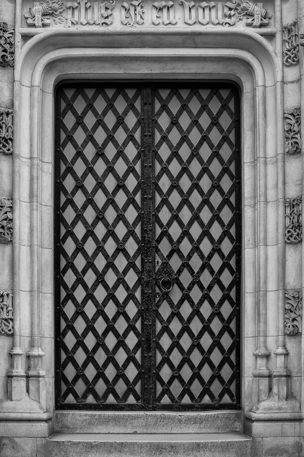 A  metal and wood lattice door  framed by stone speaks to the  rich history  of  Bruges  in  Belgium .