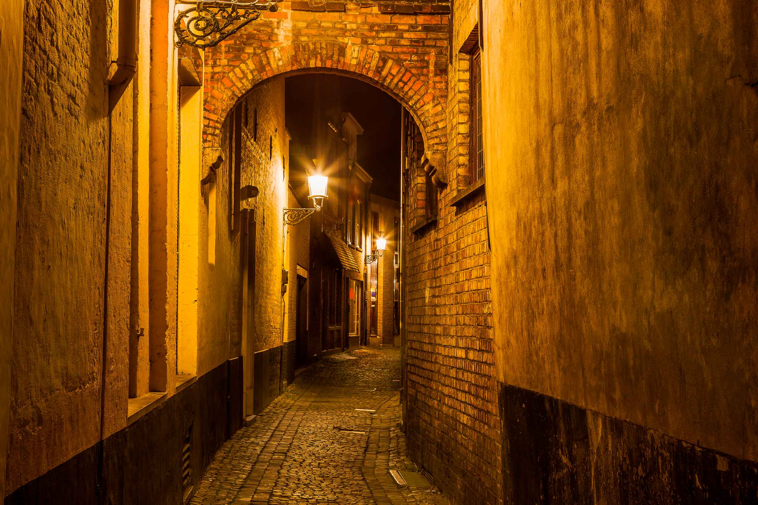 A  colorfully lit alleyway , photographed at night, in the city of  Bruges  (i.e., Brugge),  Belgium .