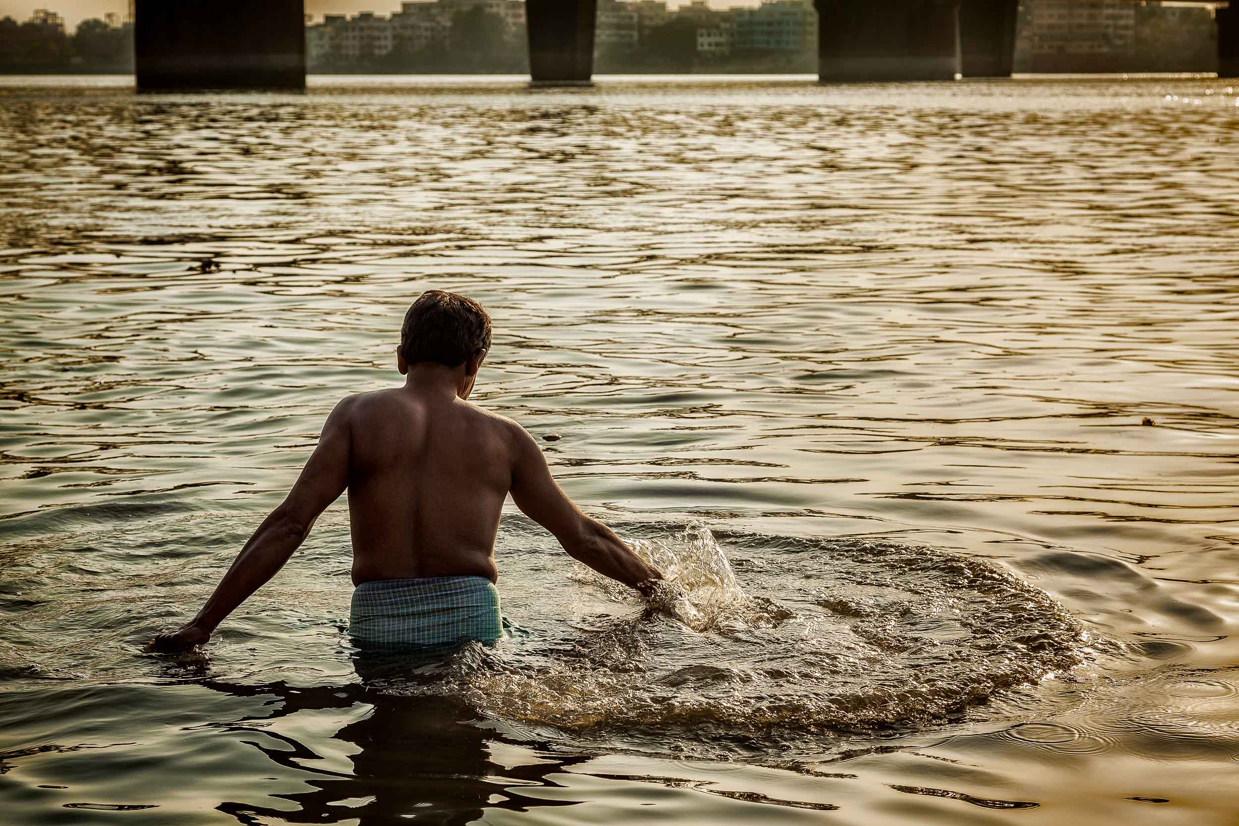 A    devotee in a moment of rapture    in the    Hooghly River    at sunset in    Kolkata, India   .