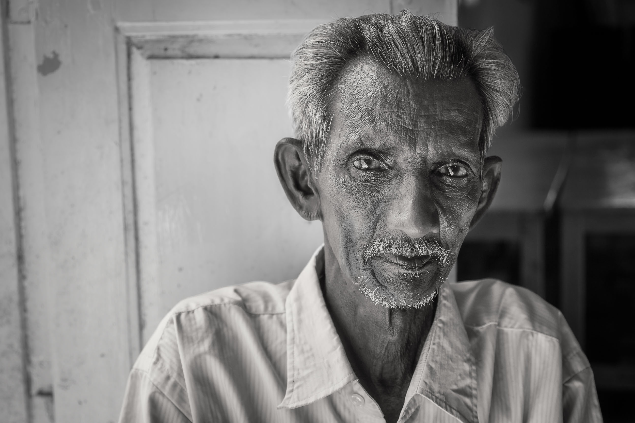 A beautiful    black and white portrait    of an    elderly man    sitting by an open doorway on the outskirts of    Chennai, India   .