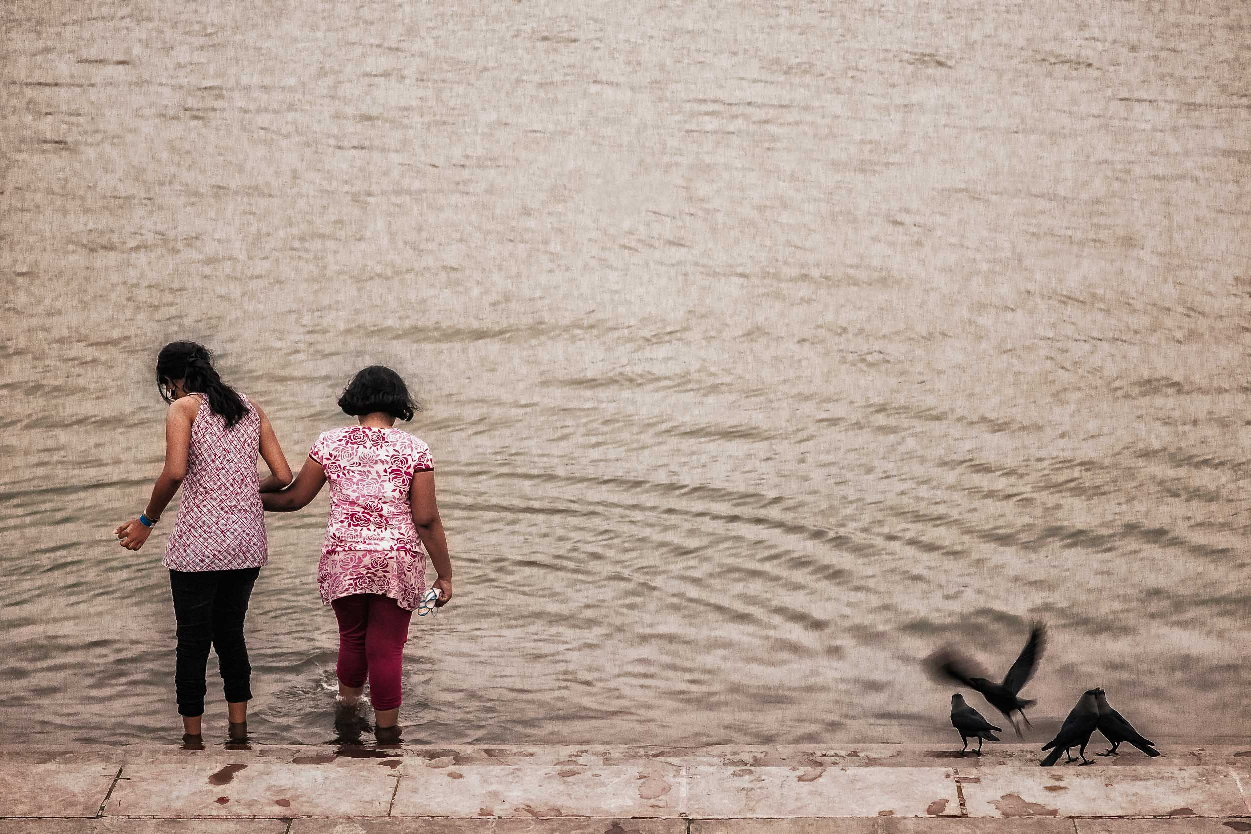Two girls    step gingerly into the    waters of the Hooghly River    in    Kolkata, India   . This is Version Two with the bottle towards the top of the frame removed.