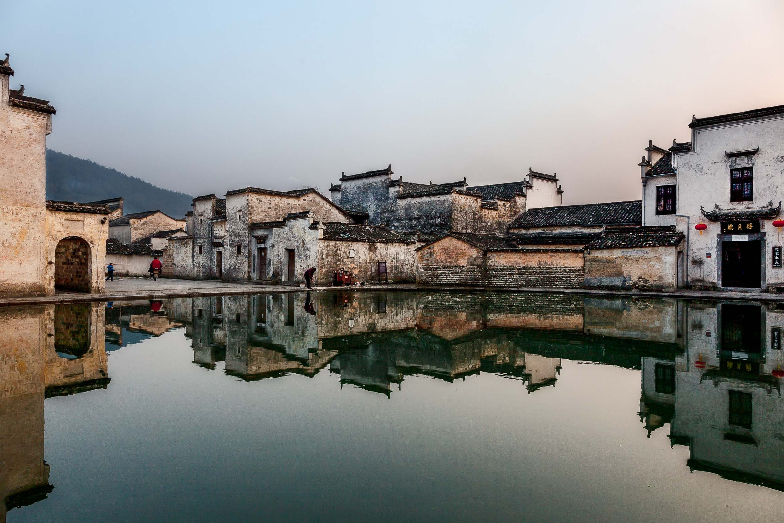 Buildings reflected    into a    pond at dusk    in the famous    Hongcun Village    in Anhui Province,    China   .