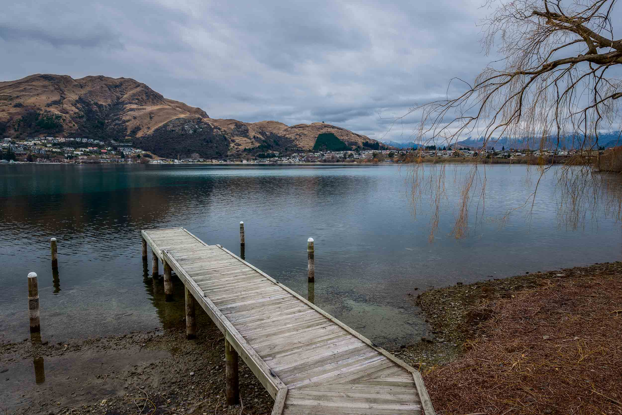 A narrow,    wooden pier    over the waters of    Lake Wakatipu    in    Queenstown, New Zealand   .