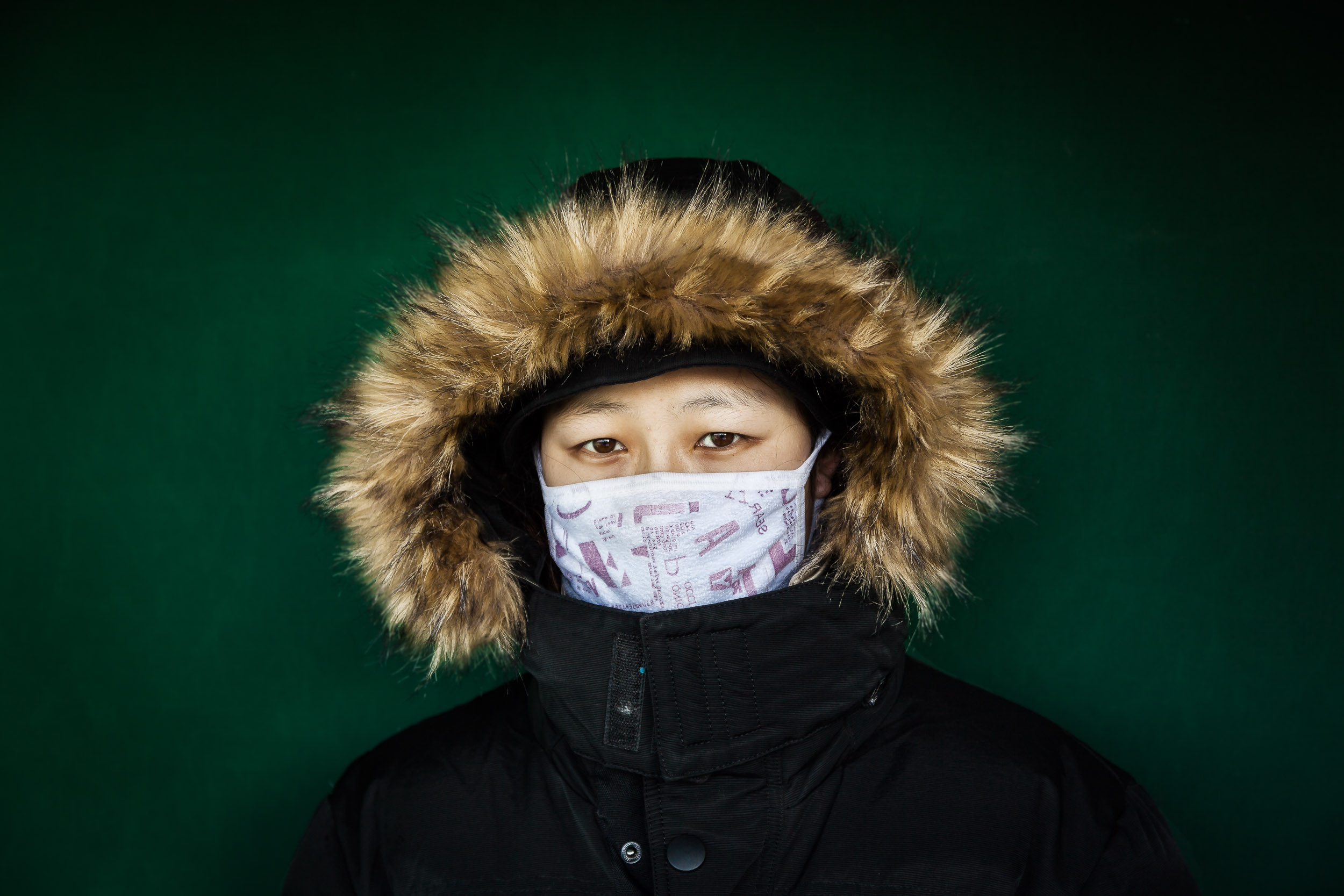 A    young woman   , wrapped in a hooded jacket, makes for a colorful composition placed against a    deep green colored wall    in    Beijing, China   .