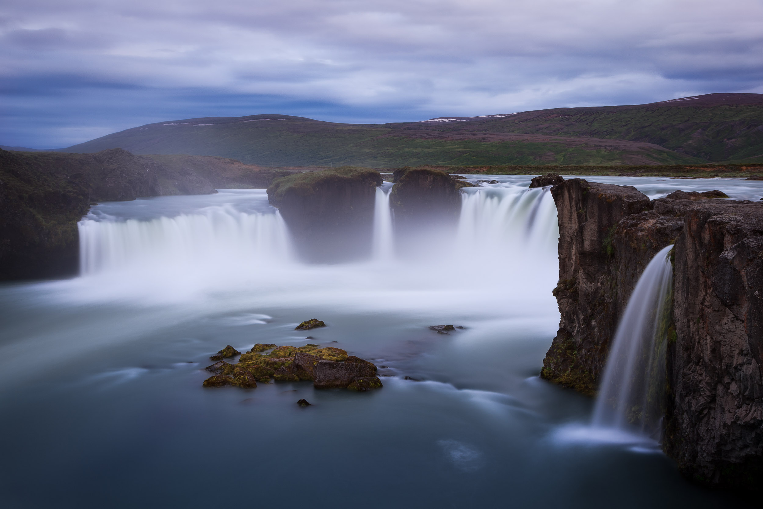 Godafoss    waterfall, under bluish grey light, has a strangely    melancholy beauty    very typical to landscapes throughout much of    Iceland   .