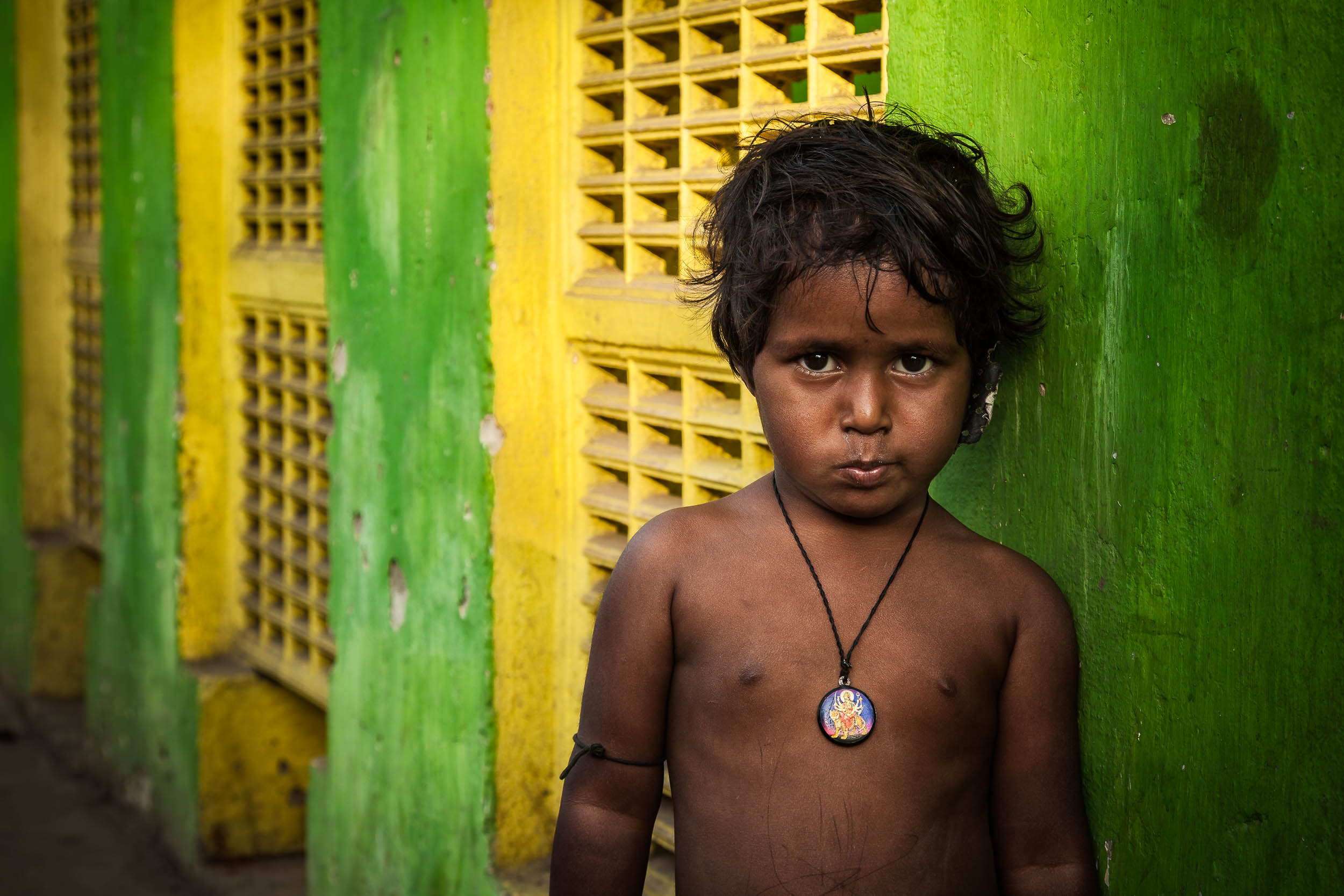 A bright    green and yellow wall    provides a colorful background for this    portrait    of a    child    at a    Kolkata    railway station in    India   .