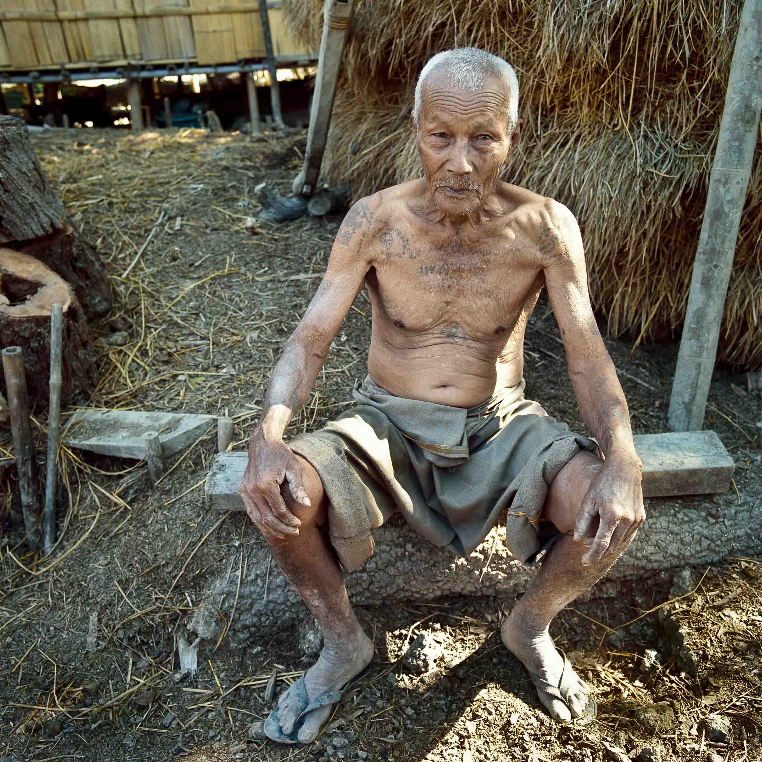 An    environmental portrait    of an    elderly man   , in his back yard, in rural    Myanmar   .