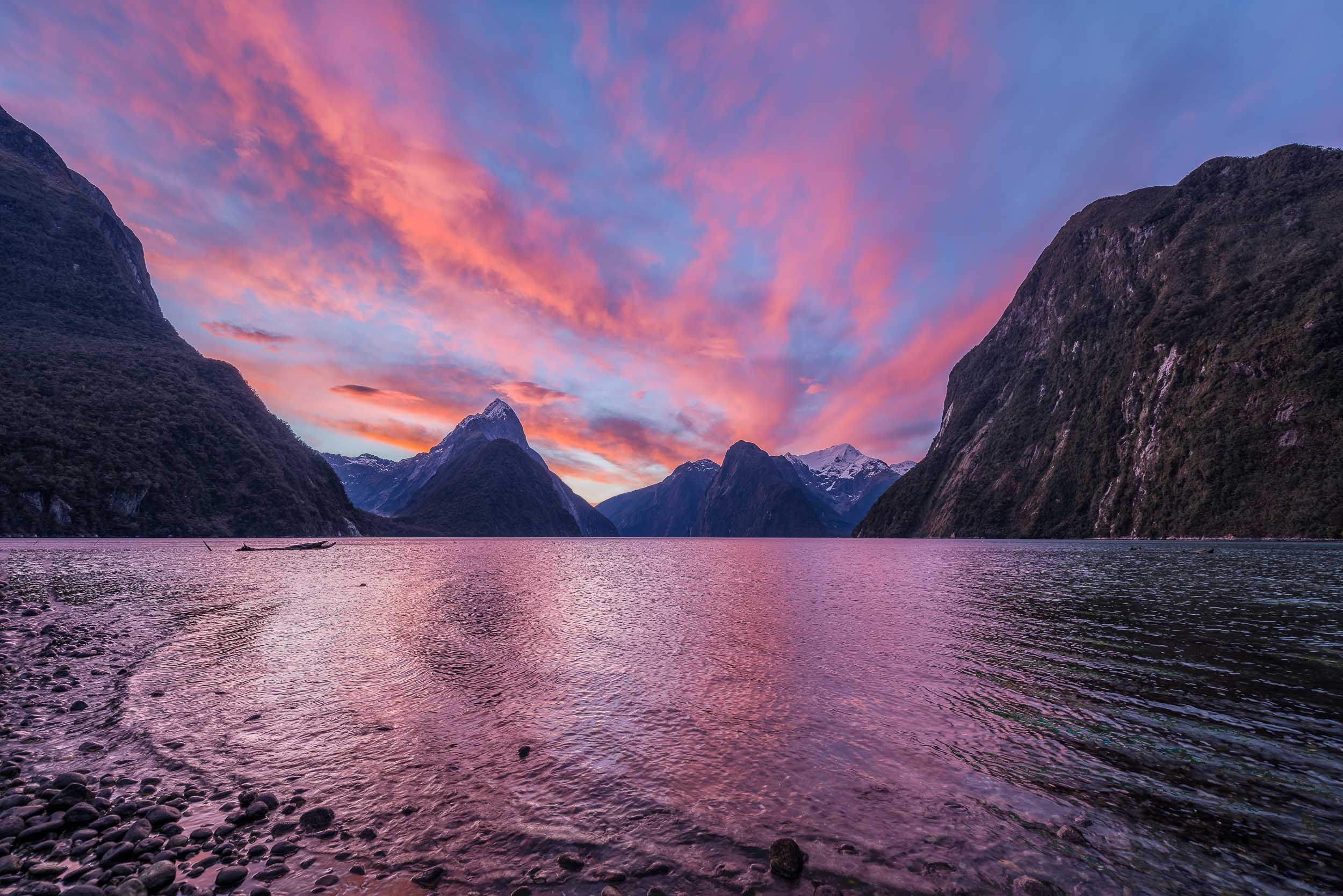 A    spectacular afterglow    illuminates the sky above    Mitre Peak    and surrounding mountains on    Milford Sound   , Fiordland,    New Zealand   .