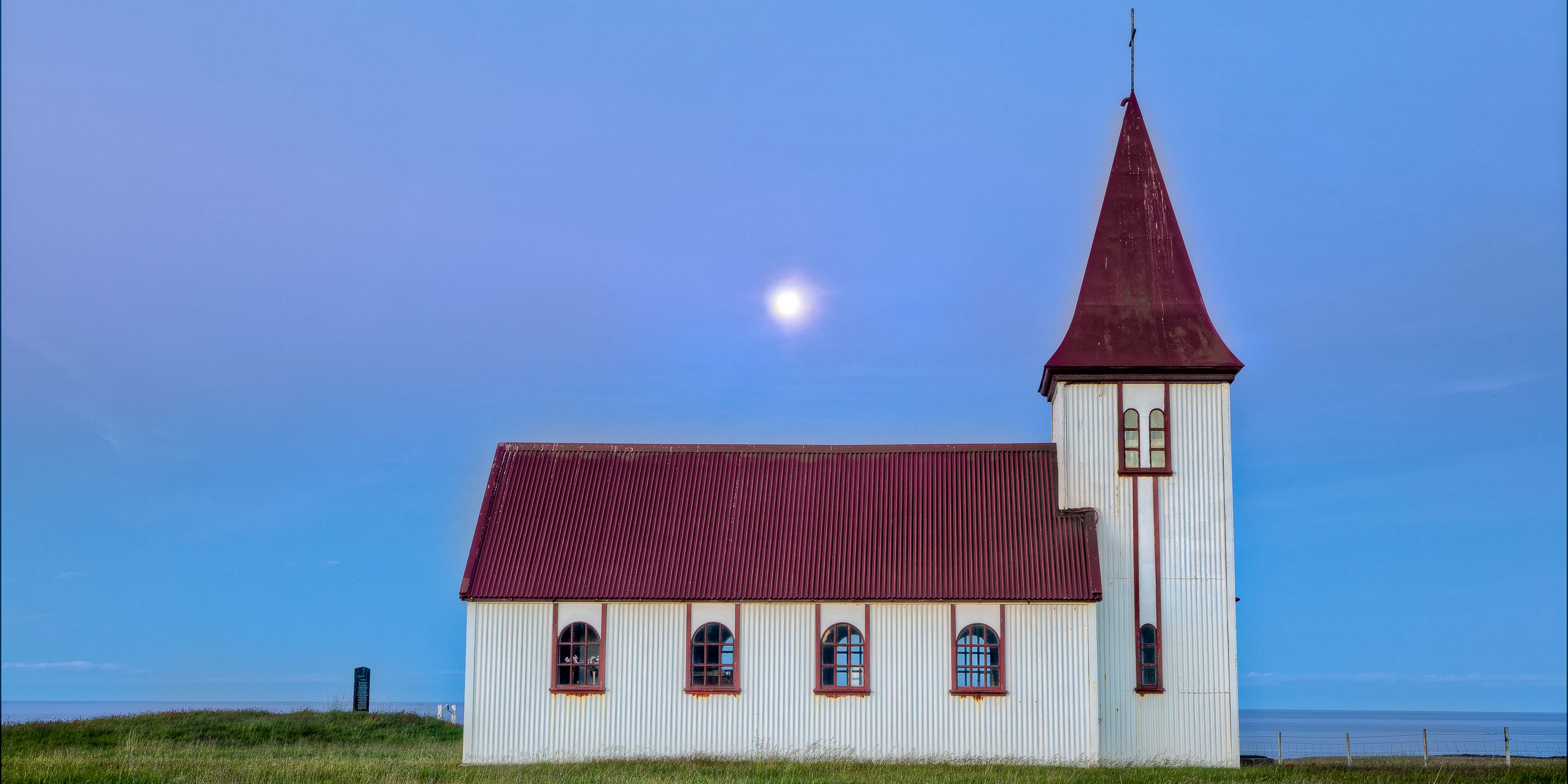 A serene moment preserved through this image of a    moon rising above a tiny church    in far north west    Iceland   .