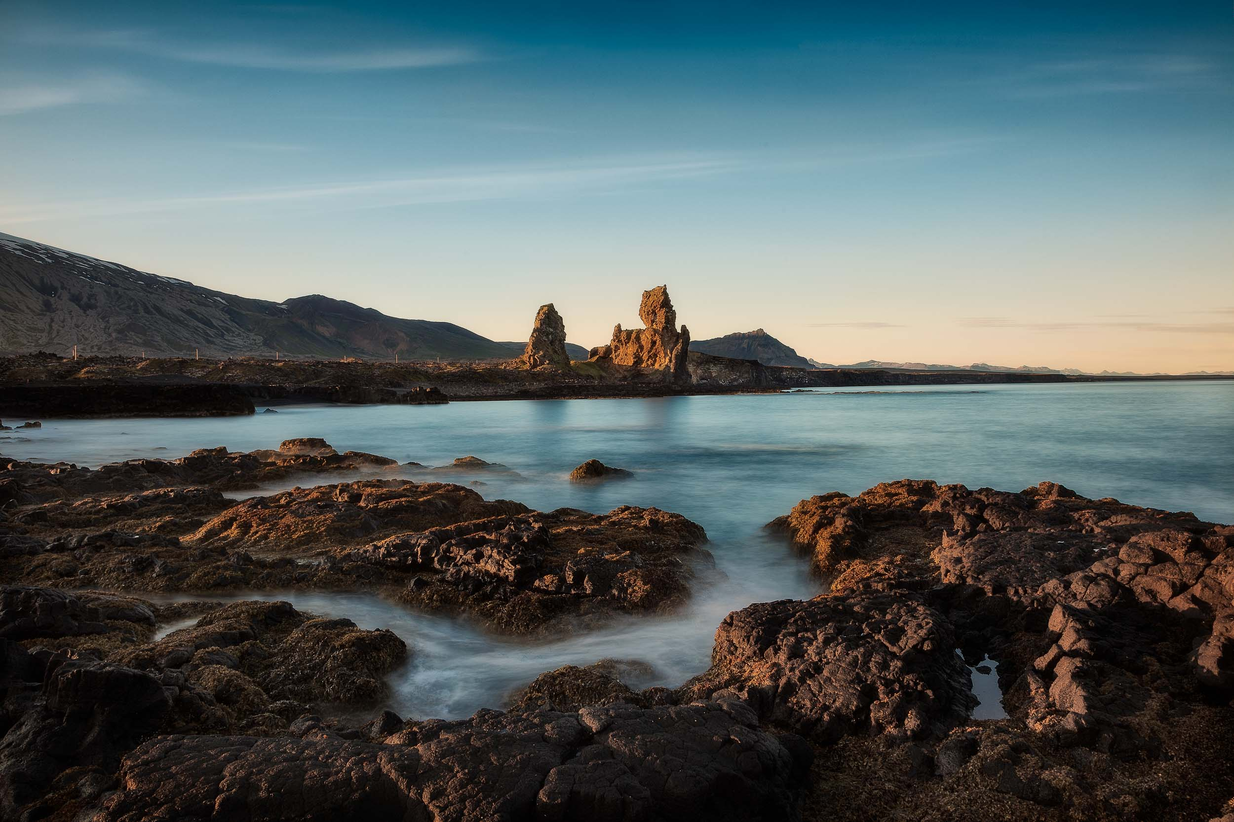 Rock formations    come alive with the    warm light of sunset    by the coast in northern    Iceland   .