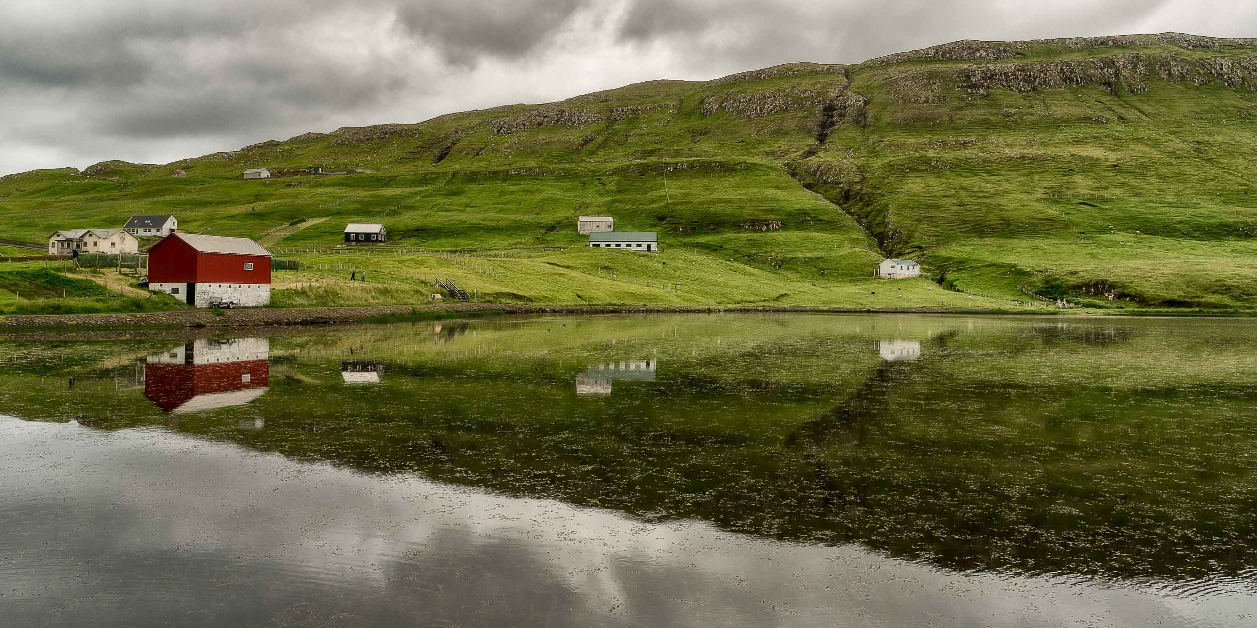 A serene scene of    farm houses    around the edges of a    lake    on the island of    Suduroy    in the    Faroe Islands   .