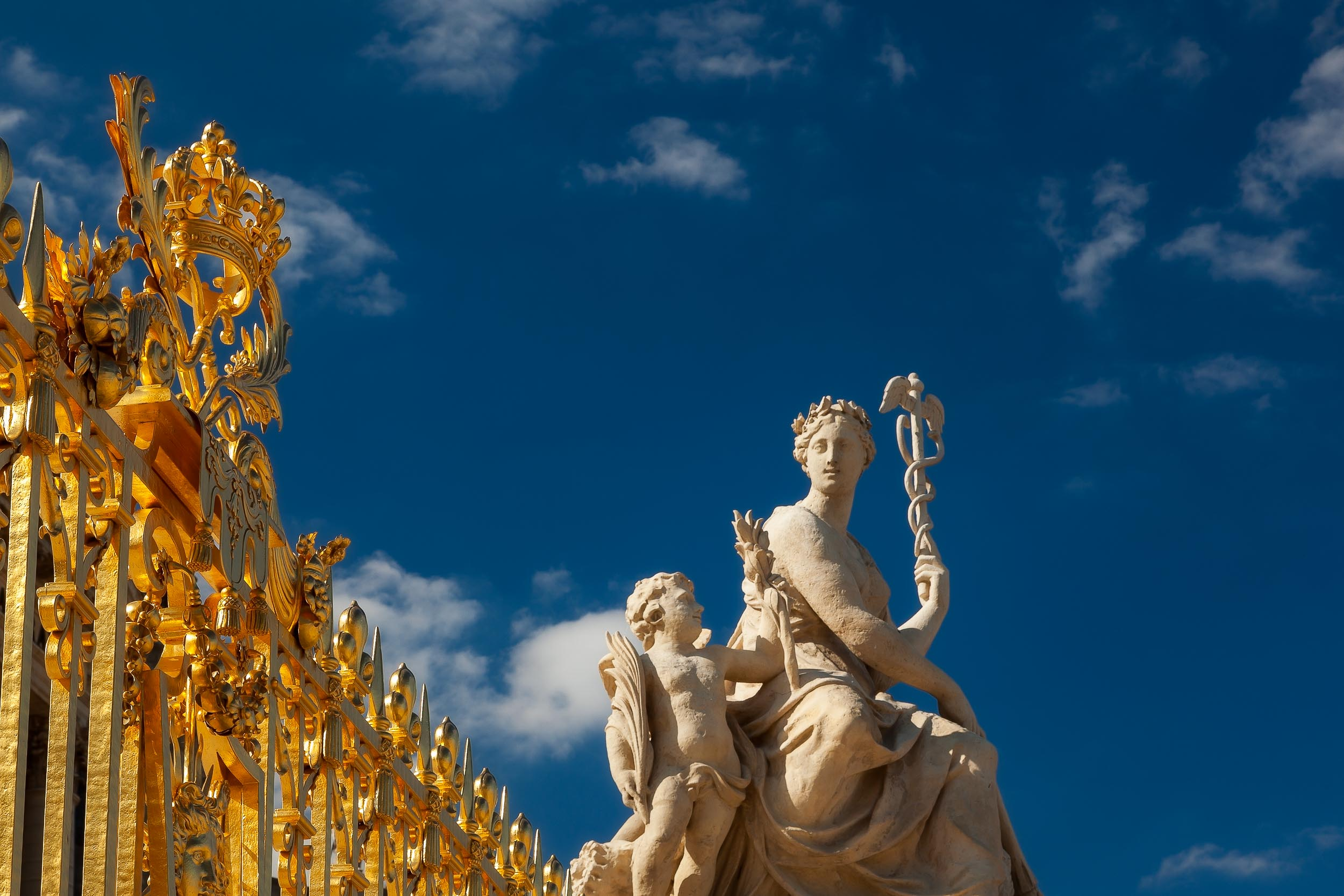 Striking light illuminates    statues    and the    golden gate    at the    Palace of Versailles, France   .