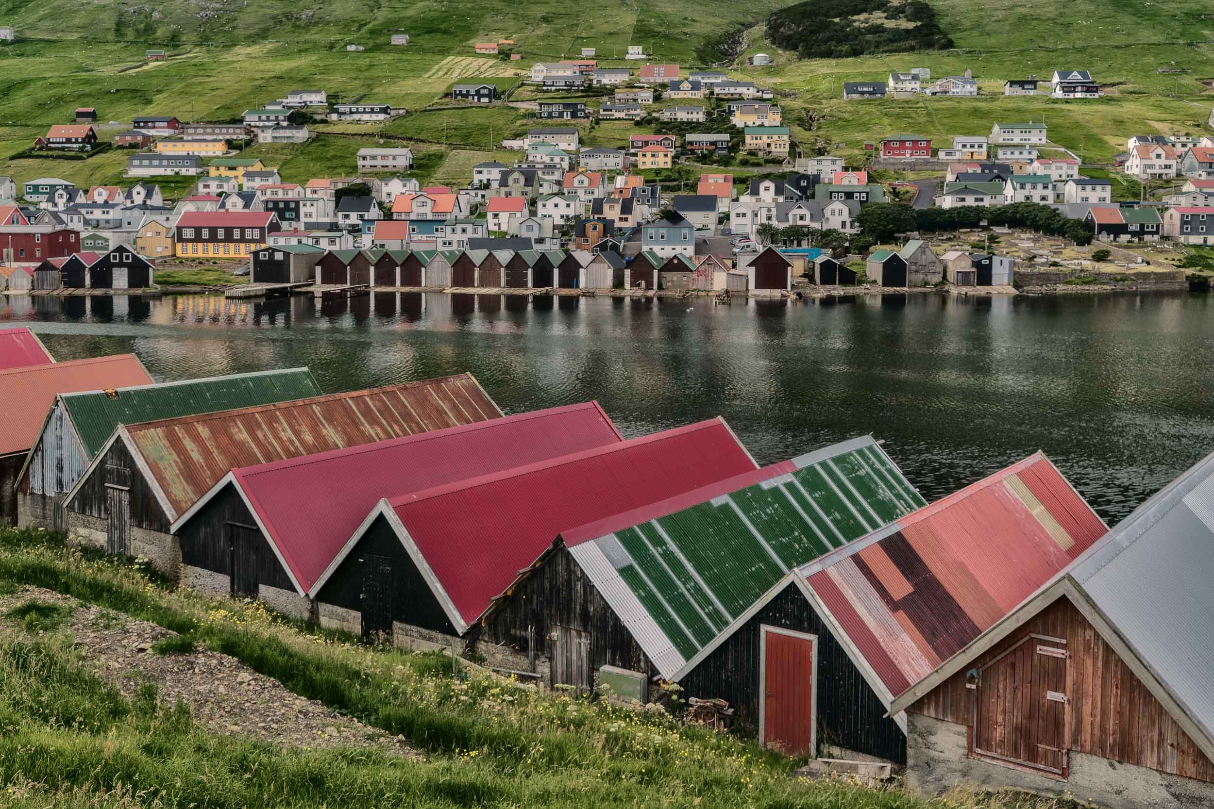 Colorful rooftops on either side of the fjord in the village of    Vágur    on the island of    Suðuroy    in the    Faroe Islands   .
