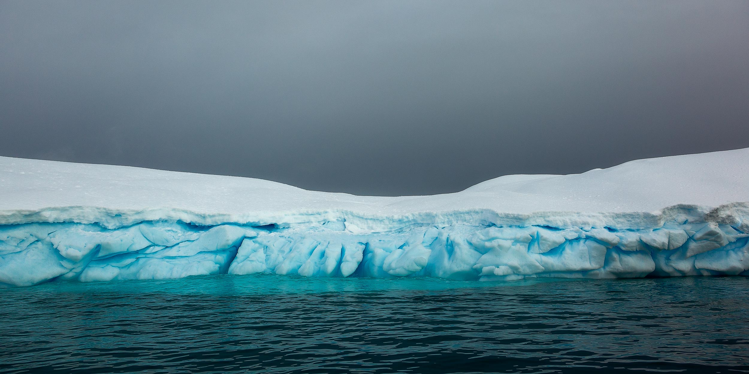 Color and texture prevail in this    panoramic view    of a large    iceberg    in    Paradise Harbour   ,    Antarctica   .
