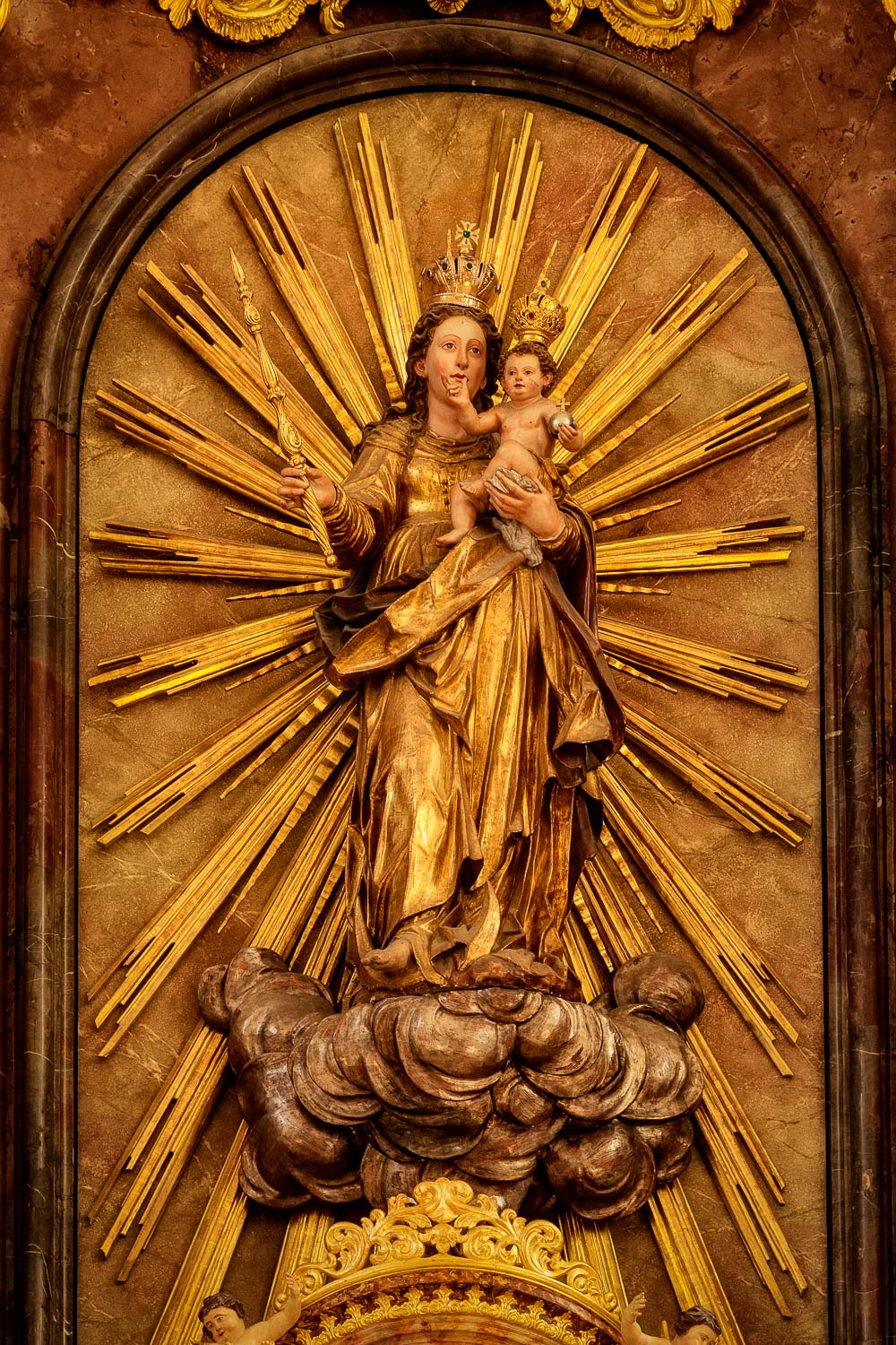 A statue of    Mary and Jesus    on an inner wall of    St. Sebastian's Church    in    Salzburg, Austria   .