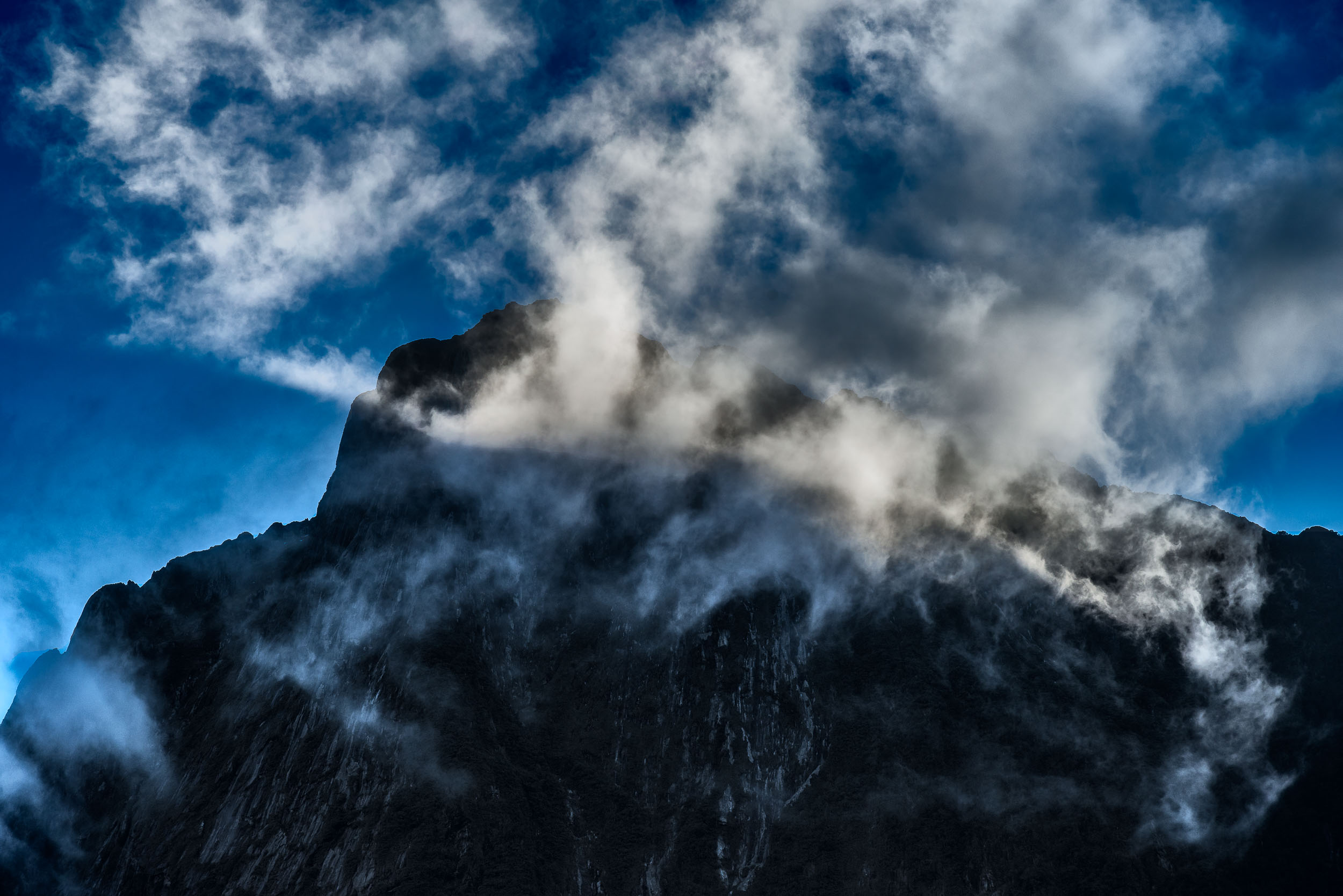A spectacular scene as    light illuminates clouds    in front of a mountain top above    Milford Sound   ,    New Zealand   .