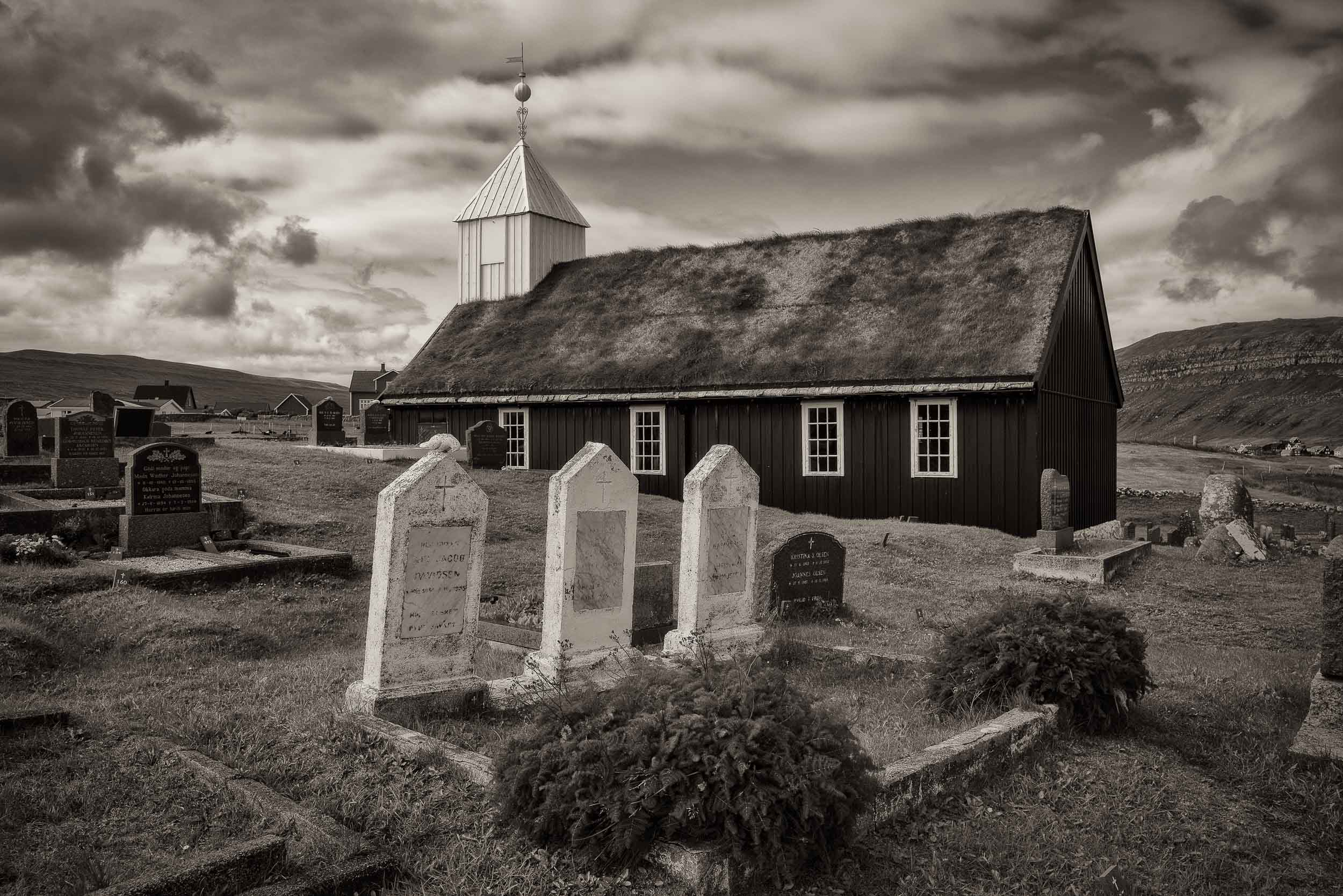 This lovely wooden church in the village of    Sandur   , on the island of    Sandoy    in the    Faroe Islands   , is a good example of    traditional church architecture    with black tarred walls topped by a    turf roof    and a white belfry.