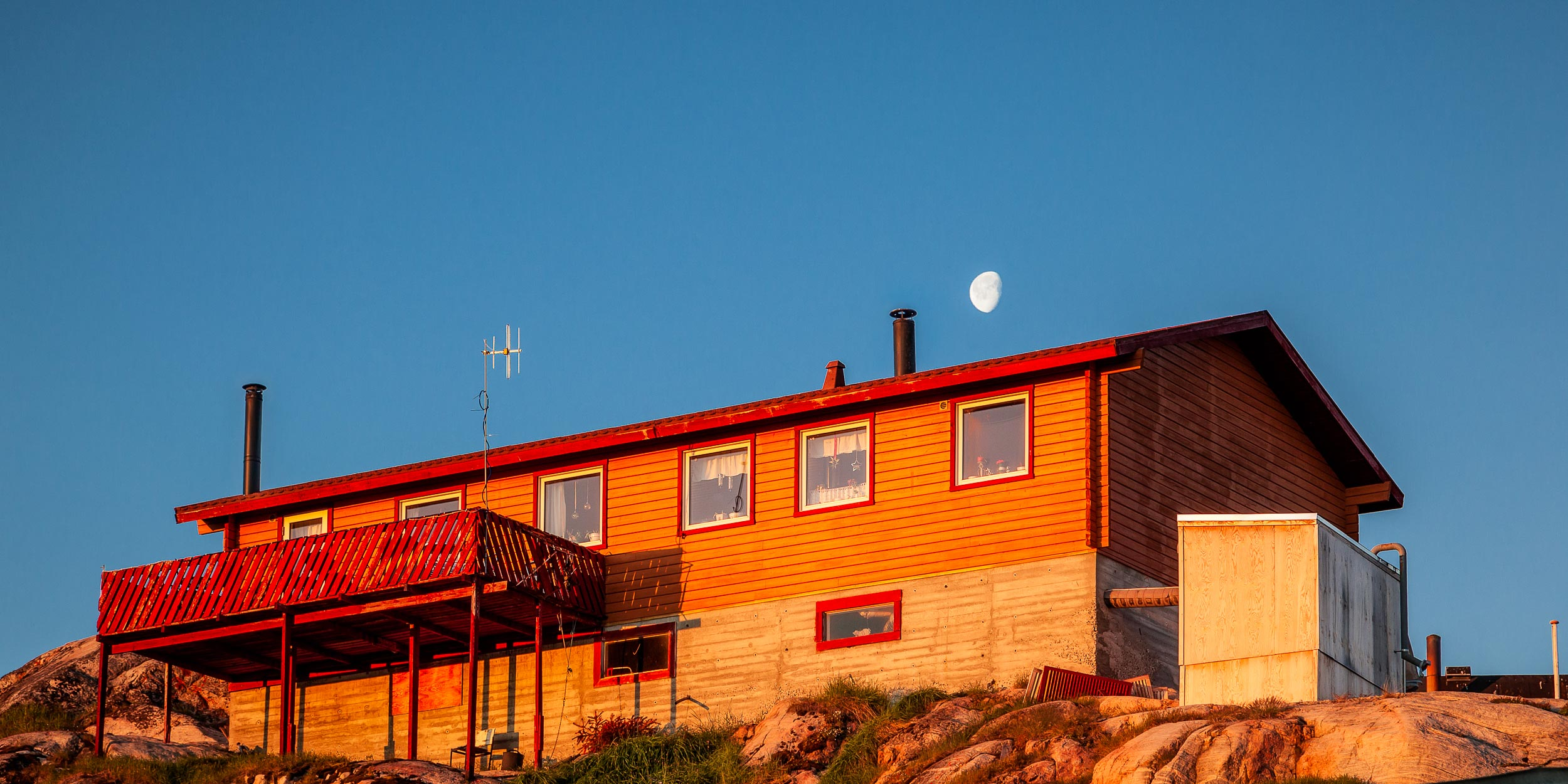 A house, glowing in the warm light of sunrise, in the town of  Ilulissat, Greenland .