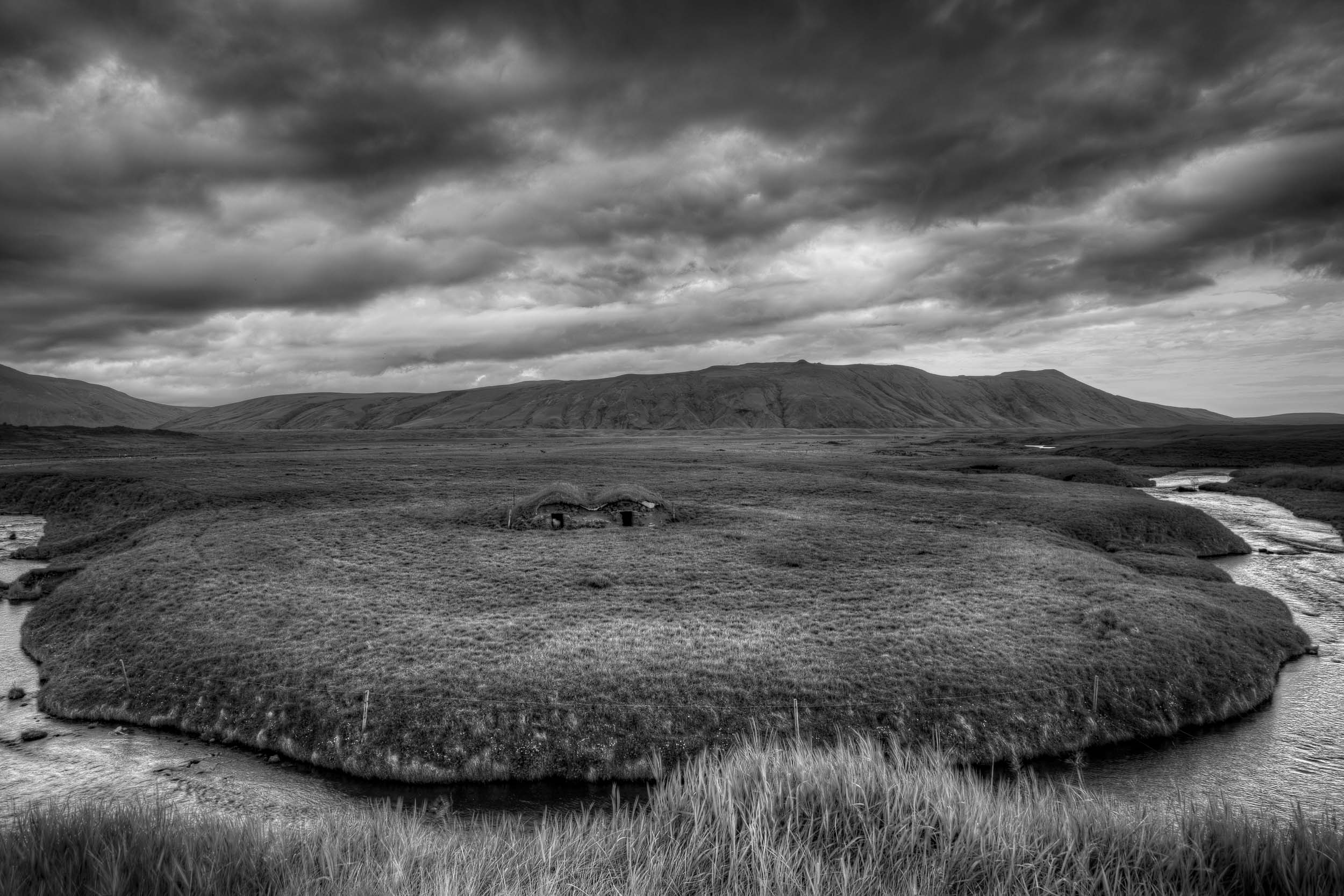 A distant    sheep shelter    in an extremely lush, well watered pasture in    rural Iceland   .