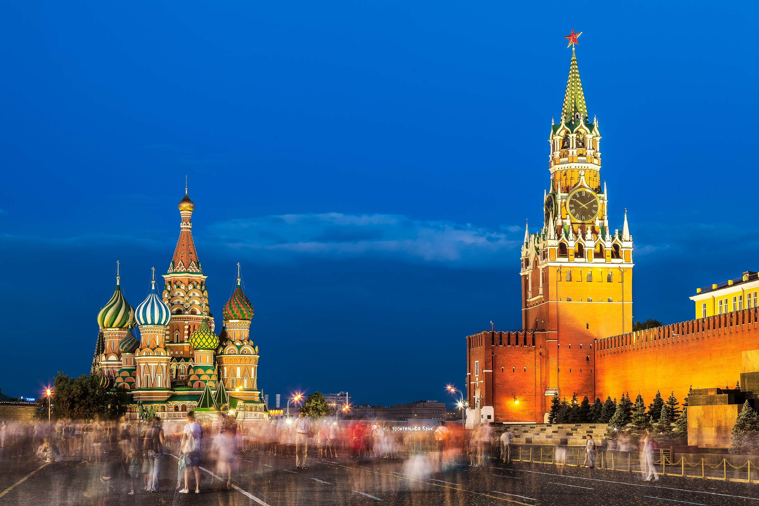 The    crowd moves silently    through the spectacular    Red Square    in    Moscow   , Russia on a balmy summer evening flanked by the magnificence of    St. Basil's Cathedral    and the    Kremlin   .