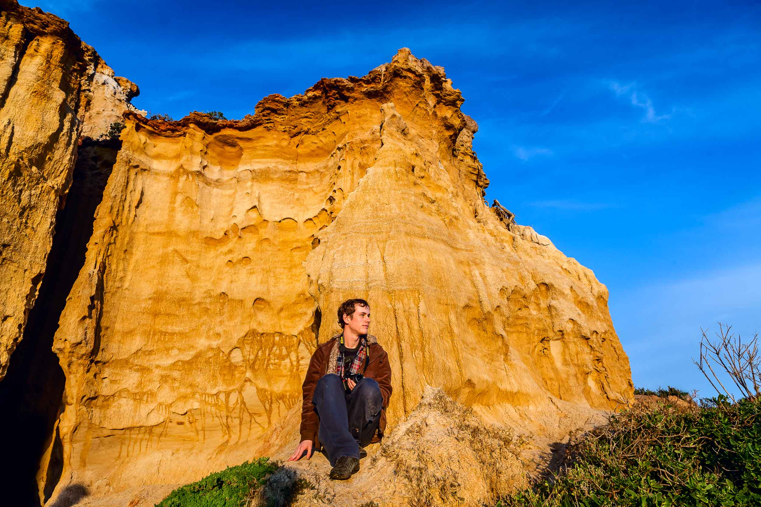 A young man looks out towards    Half Moon Bay    from the cliffs above the beach.