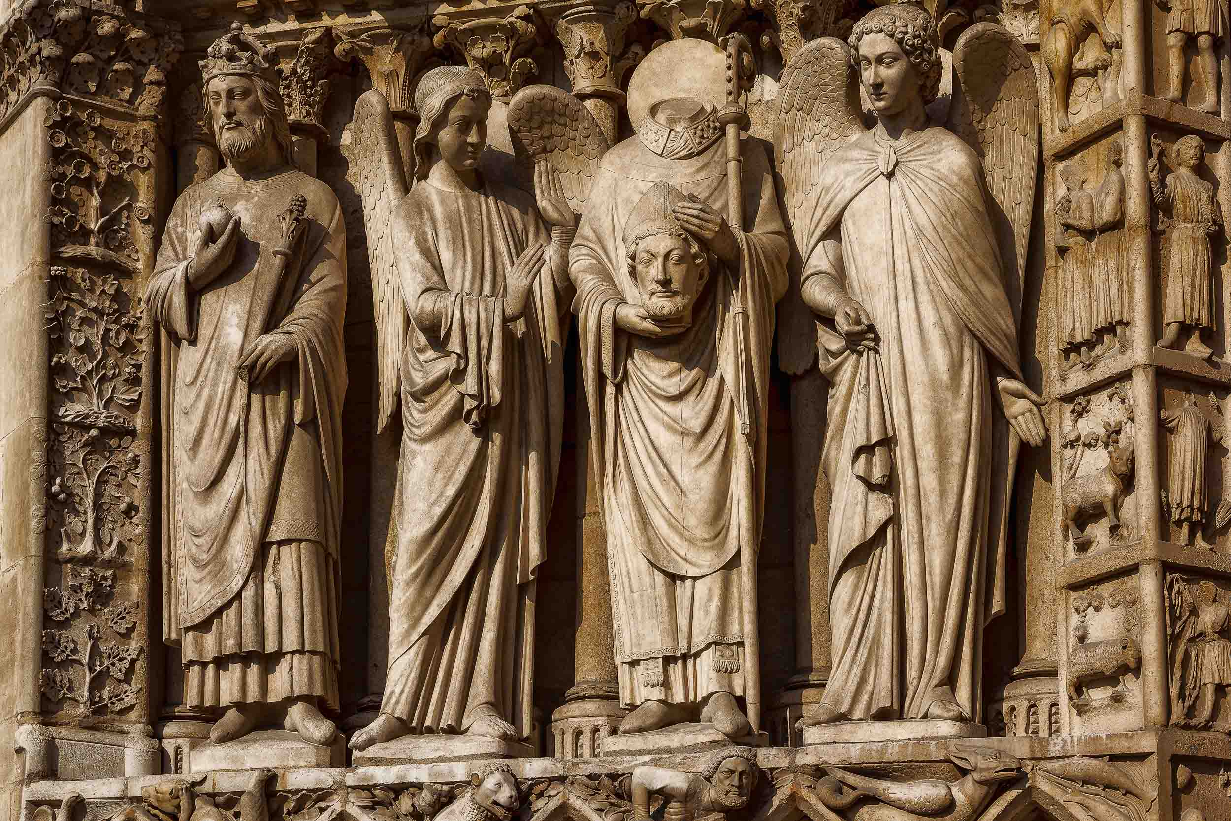 Wonderfully detailed    statues    high up on the facade of the    Notre Dame Cathedral    in    Paris, France   .