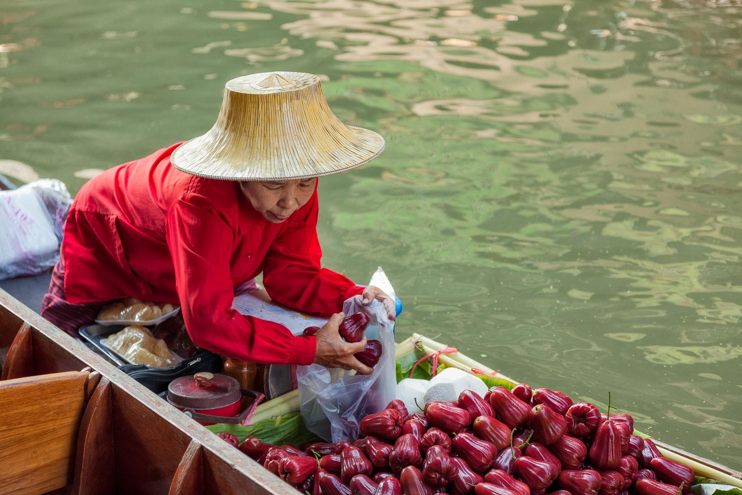 An elderly    female food vendor    selling produce from her    long-tail boat    at the popular    Damnoen Saduak Floating Market    near    Bangkok, Thailand   .