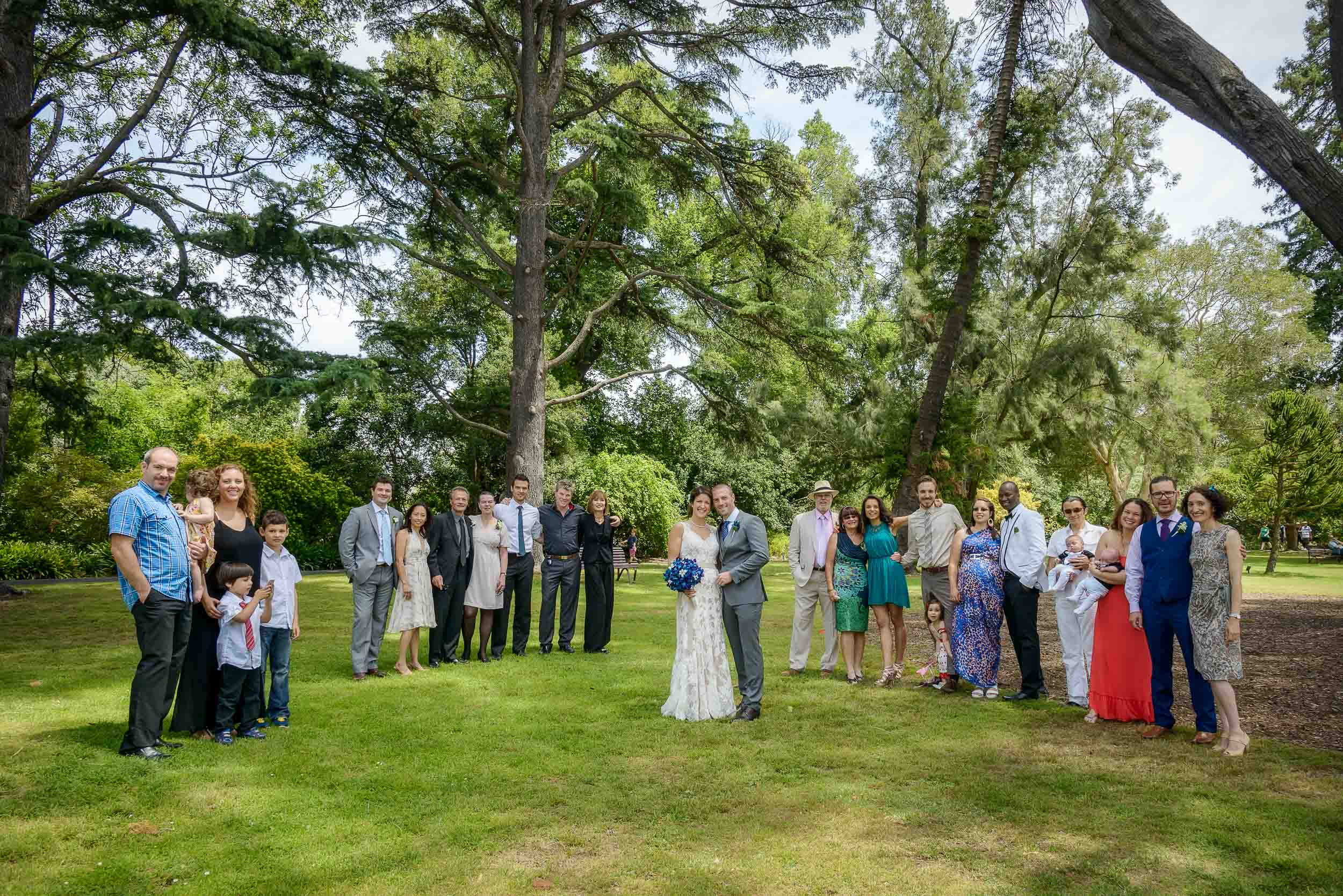 A photo with members from both the    bride and groom's extended families    at a lovely outdoor location.