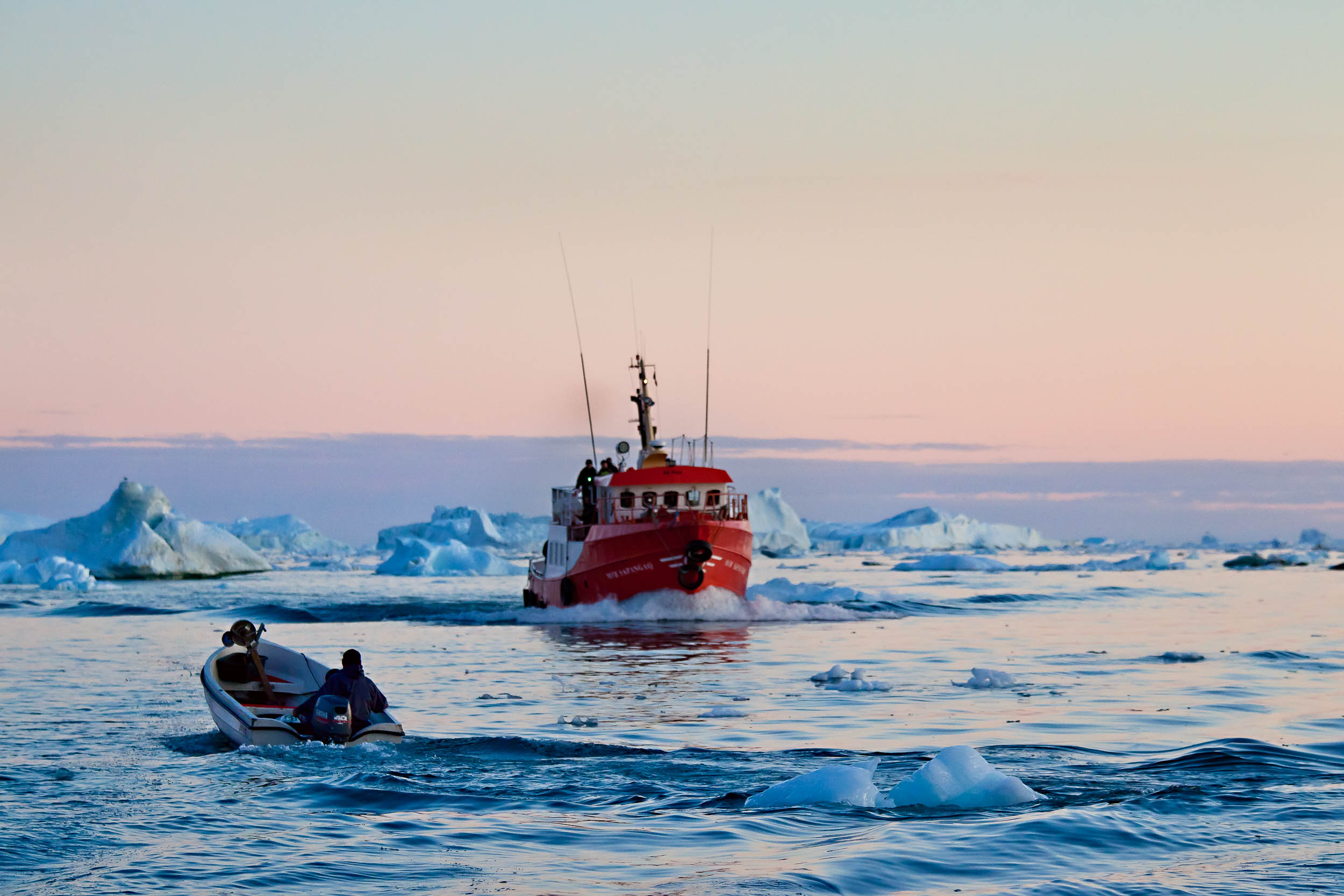 A l   one fisherman    heads out to sea, just as a larger vessel returns,    Disko Bay, Greenland   .
