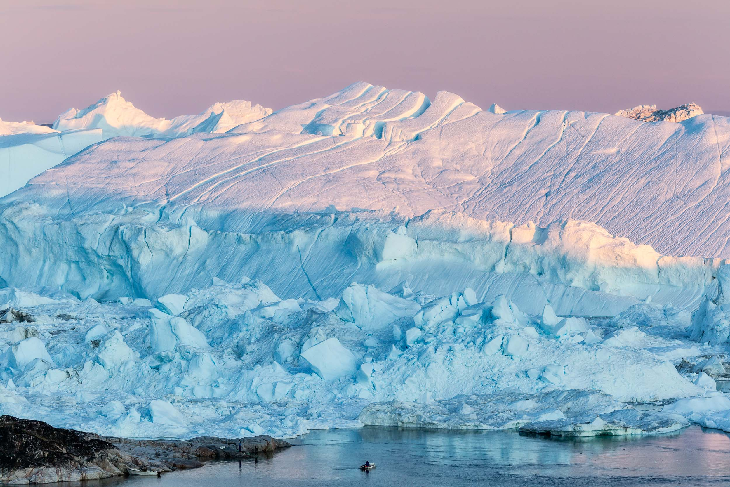 A    fisherman    and his boat is dwarfed by    massive icebergs    on the edge of    Disko Bay    near the town of    Ilulissat    in    Greenland   .