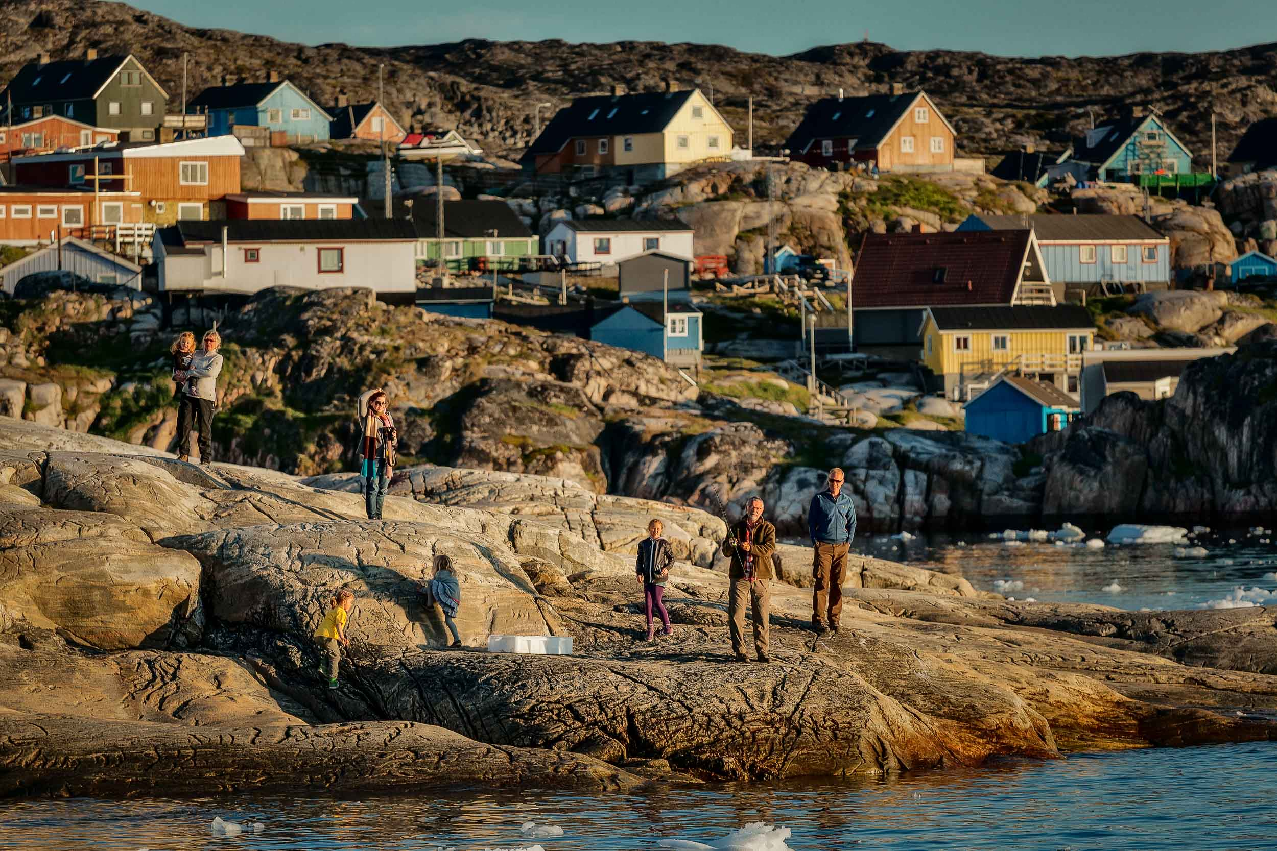 A    family    and a    fisherman    by the shores of    Ilulissat, Greenland    under the    midnight sun   .