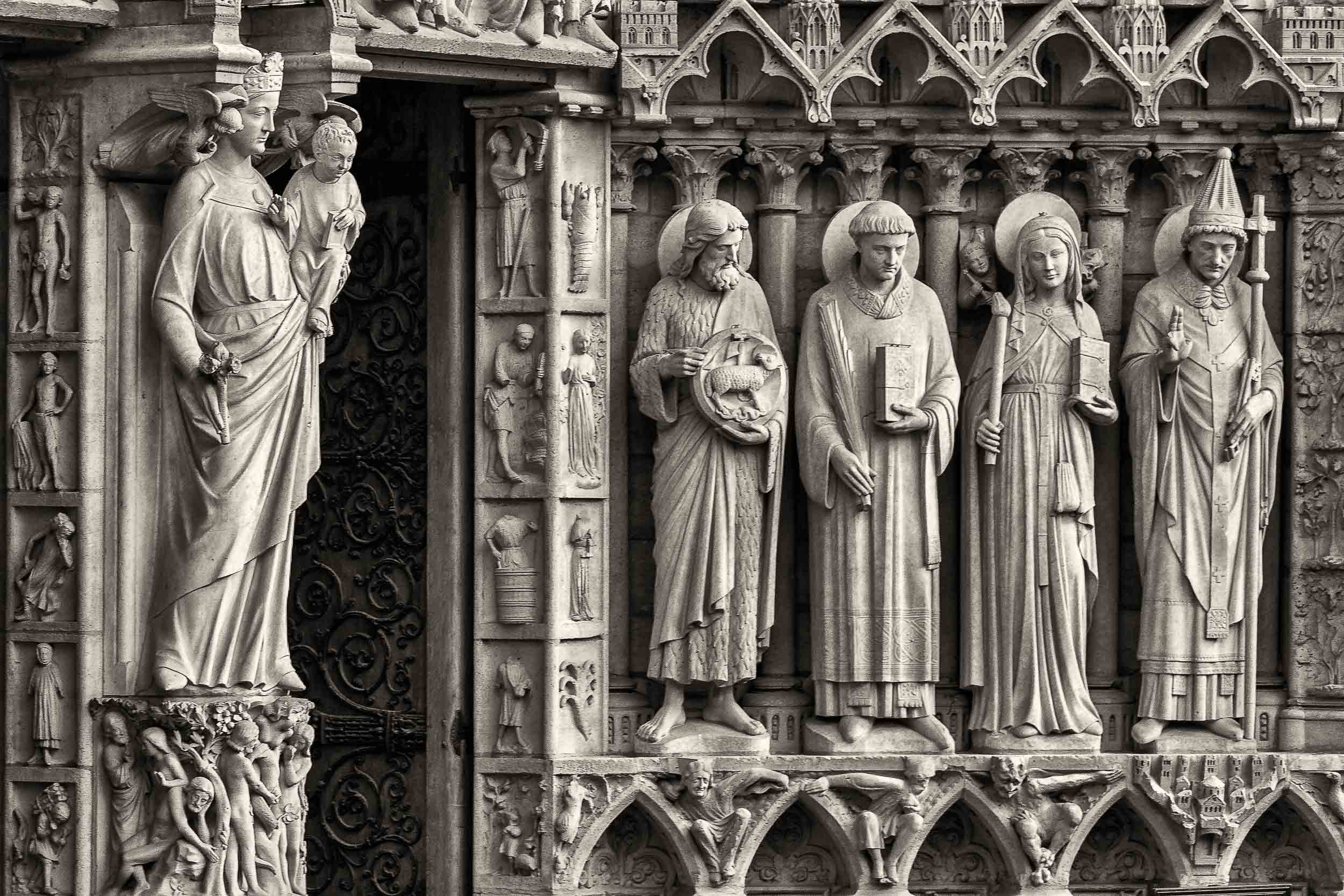Beautifully expressive    Christian statues    overlooking visitors entering    Notre Dame Cathedral    in Paris, France.