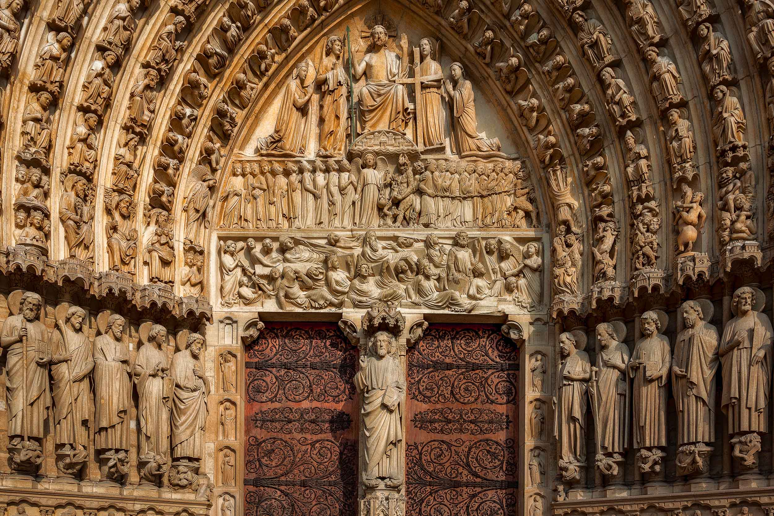 Intricately    carved statues   , under late afternoon light, frame an entrance to the spectacular    Notre Dame Cathedral    in Paris, France.