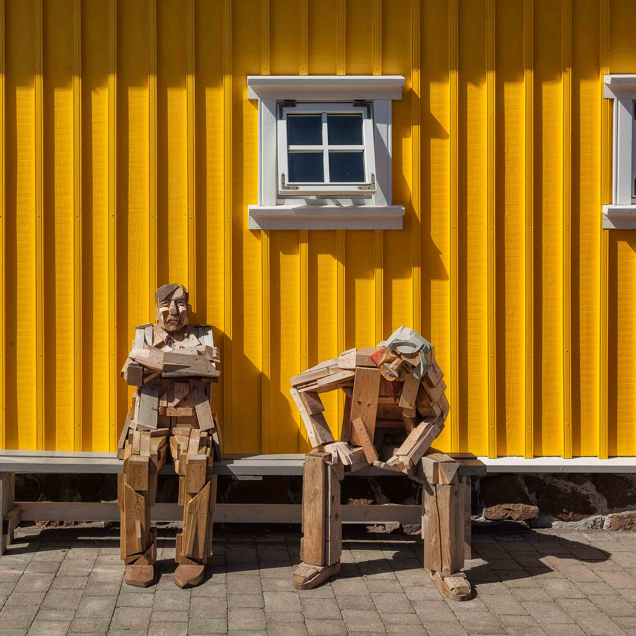 Two    wooden statues    at rest outside the    Hannes Boy Cafe    in    Siglufjordur, Iceland   .