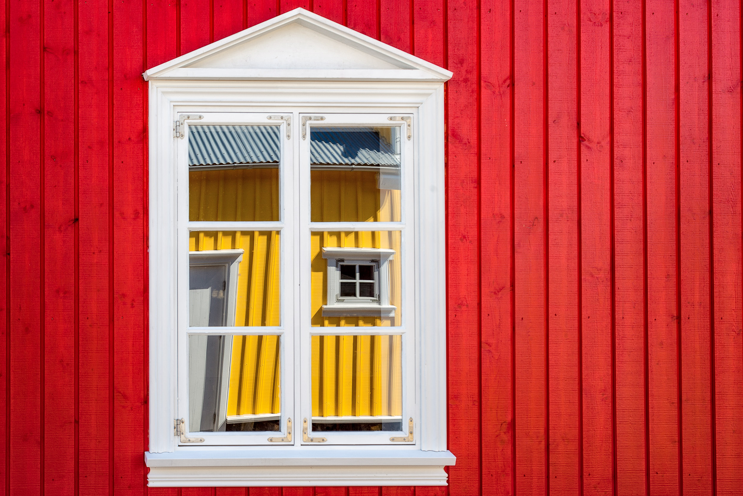 A    brightly painted wall    reflected in a window in the seaside town of    Siglufjordur    in    northern Iceland   .
