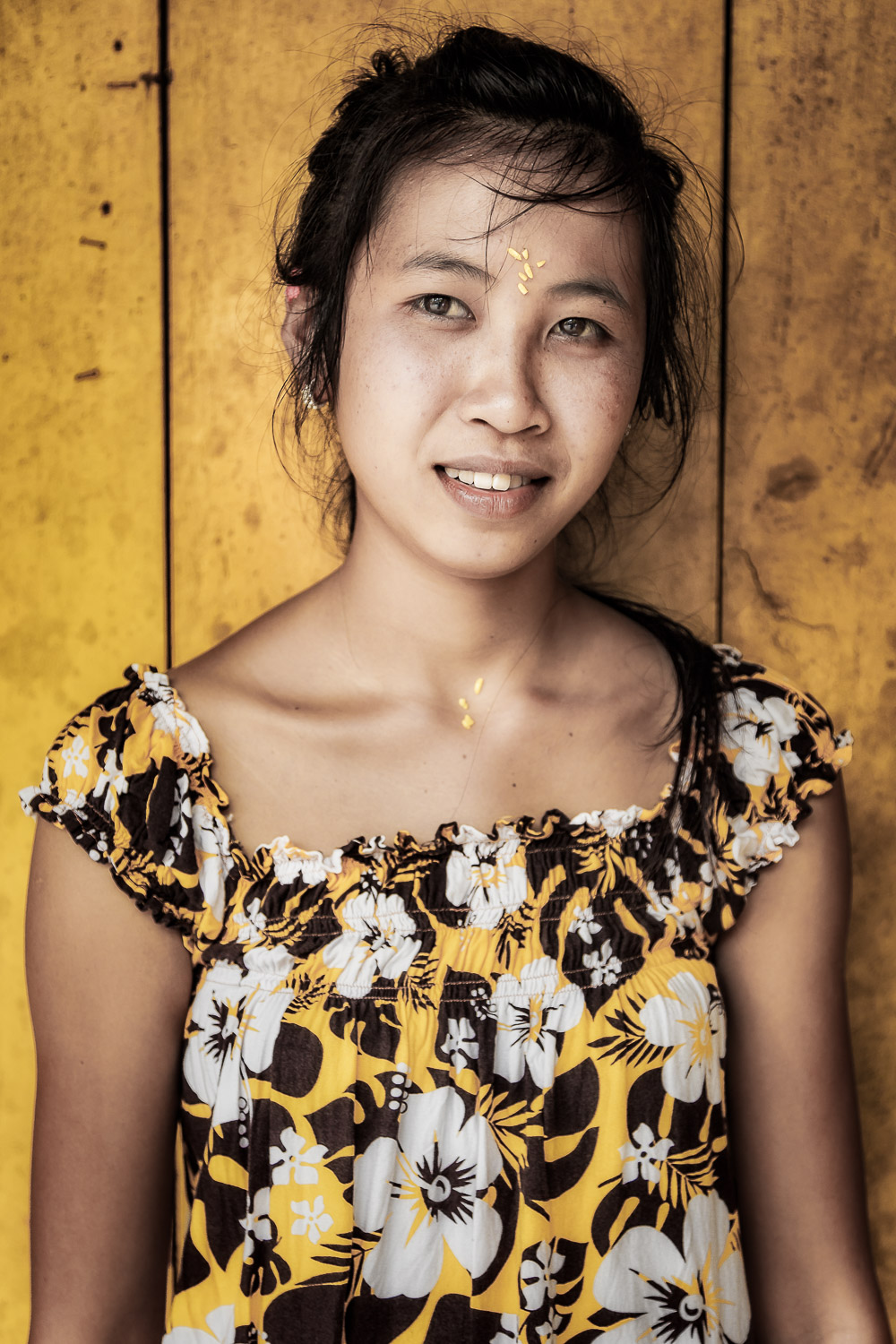 This version of the image of a    young Balinese woman    dressed in yellow and standing against a yellow painted wall in rural    Bali, Indonesia    features a more desaturated color palette in addition to a vignette to darken the areas of the image surrounding her face.