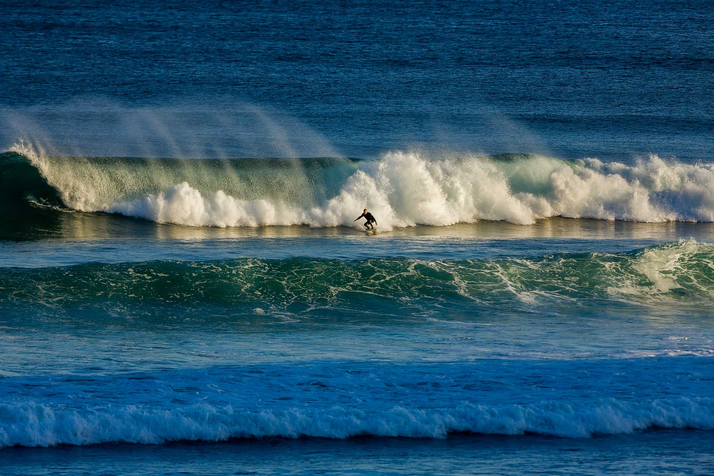 A    surfer   , catching some waves while being illuminated with    late afternoon light    at    Bells Beach, Australia   .