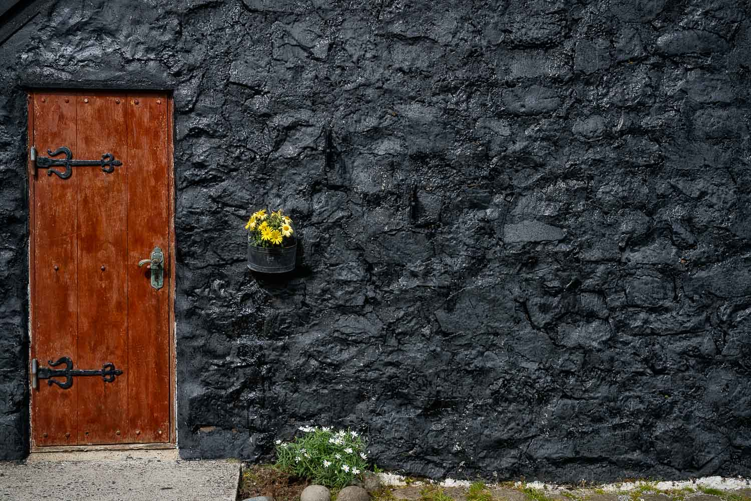 The    front door    and black tar wall of a traditional turf roof house in the    Faroe Islands   .