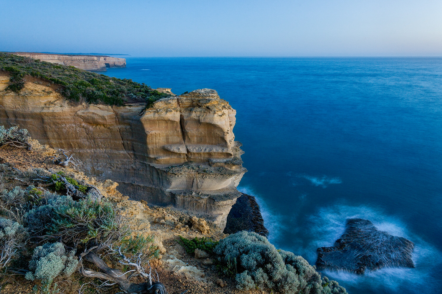 A view of    sandstone cliffs    and sea at days end in the    Port Campbell National Park    along the    Great Ocean Road    in Australia.